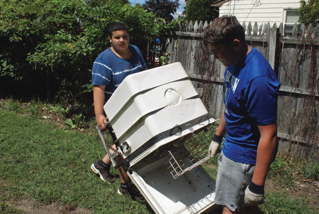 TEAMWORK: Lifting a complete dishwasher, which was discarded behind Presidential Place in Cranston, are sophomore Devin Smith and freshman Brady Kitterick of the Cranston High School East football team.