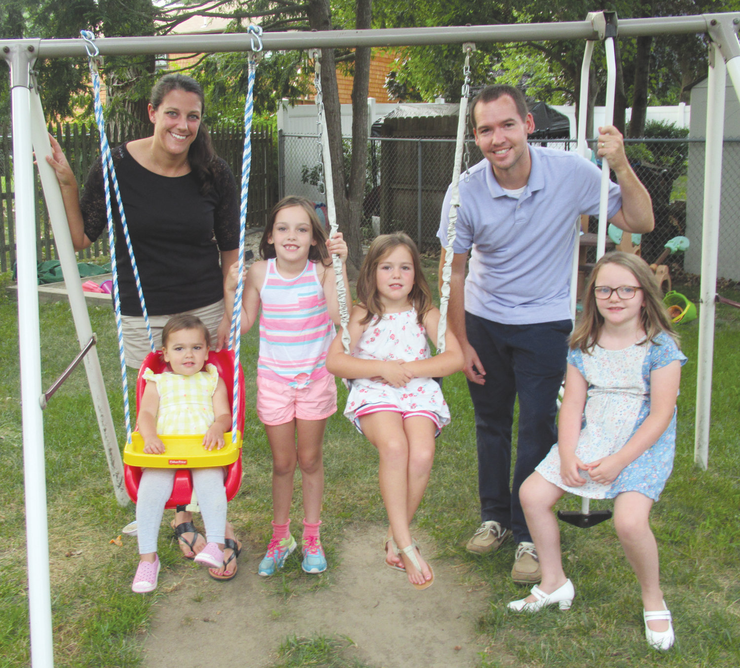 FAMILY FUN: Matthew Yates, the new principal at Winsor Hill Elementary School, and his wife, Jackie, spent time Tuesday evening on the family swing set in Warwick prior to taking daughters Adelynn, Grace, Vivian and Claire for some ice cream.