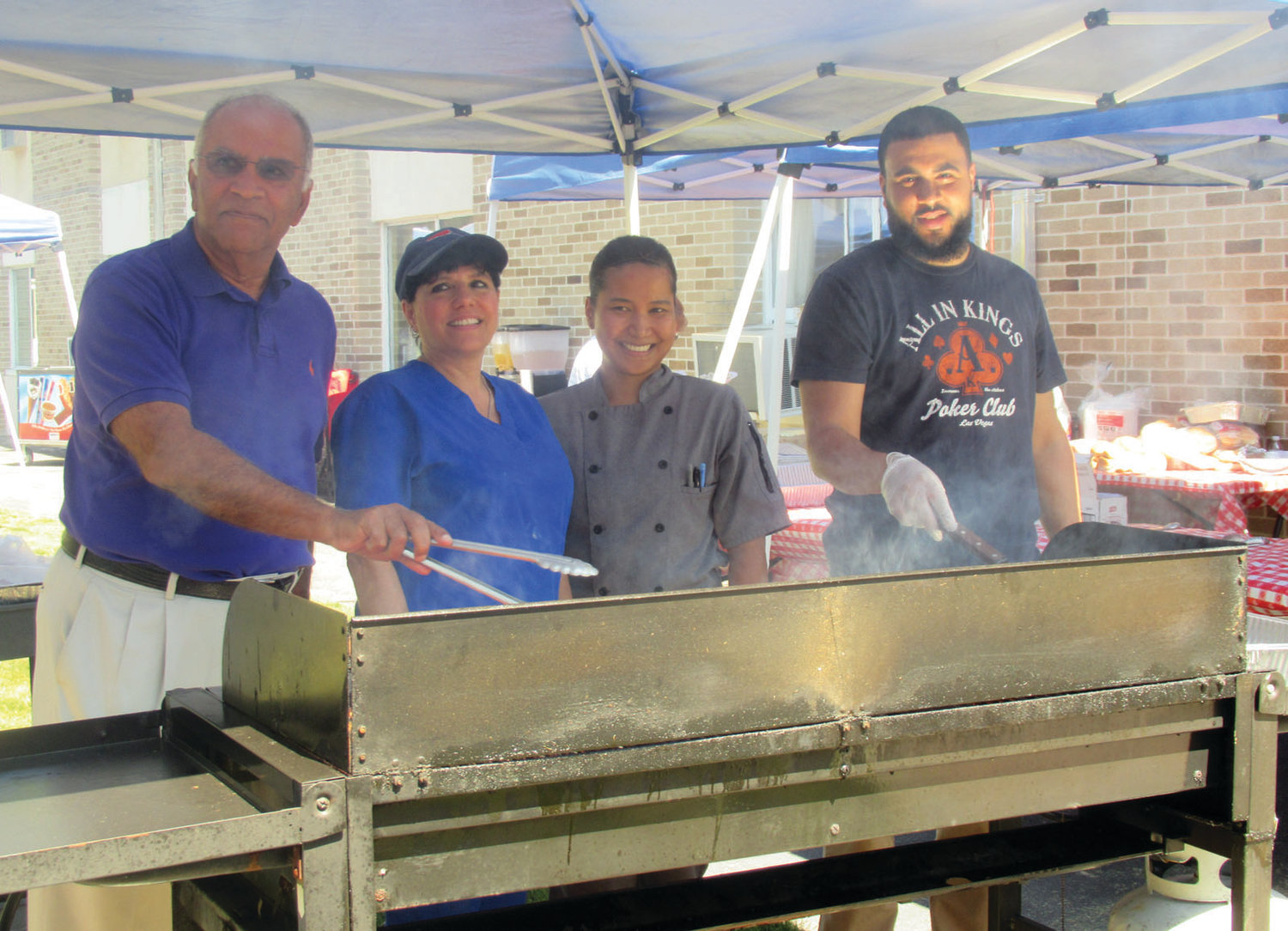 DELIGHTFUL DUTY: Akshay Talwar, left, owner and CEO of the Briarcliffe Campus, joins staffers Sharon Botelho, Henary Yan and Brian Razzino at the grill during Friday's old-fashioned cookout.
