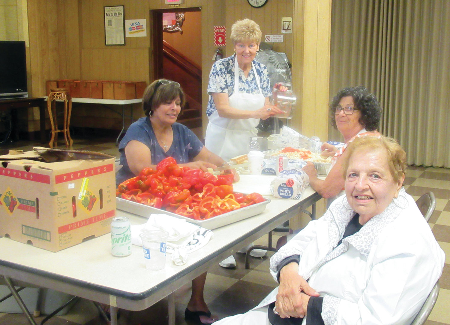 CAROL'S CORNER: Longtime Our Lady of Grace chef Carol Cambio, right, is all smiles during Tuesday's work session, which included Phyllis Gelsomino, Marilyn Delmonico and Cathy Macari cutting up red peppers for the parish's famous sausage and pepper sandwiches that will be served this weekend during the 91st Italian Feast and Festival.