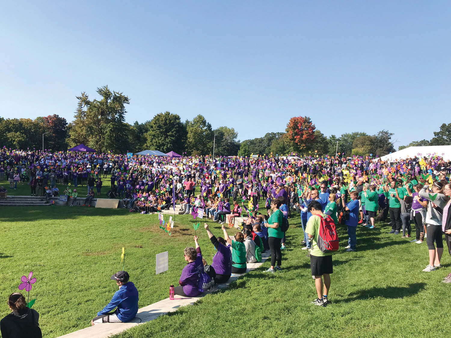"POWERFUL MOMENT: Walk to End Alzheimer's attendees hold up their flowers as part of the Promise Garden experience. ""It's a beautiful sight. It's a powerful thing to see,"" Rob LeBlanc said."