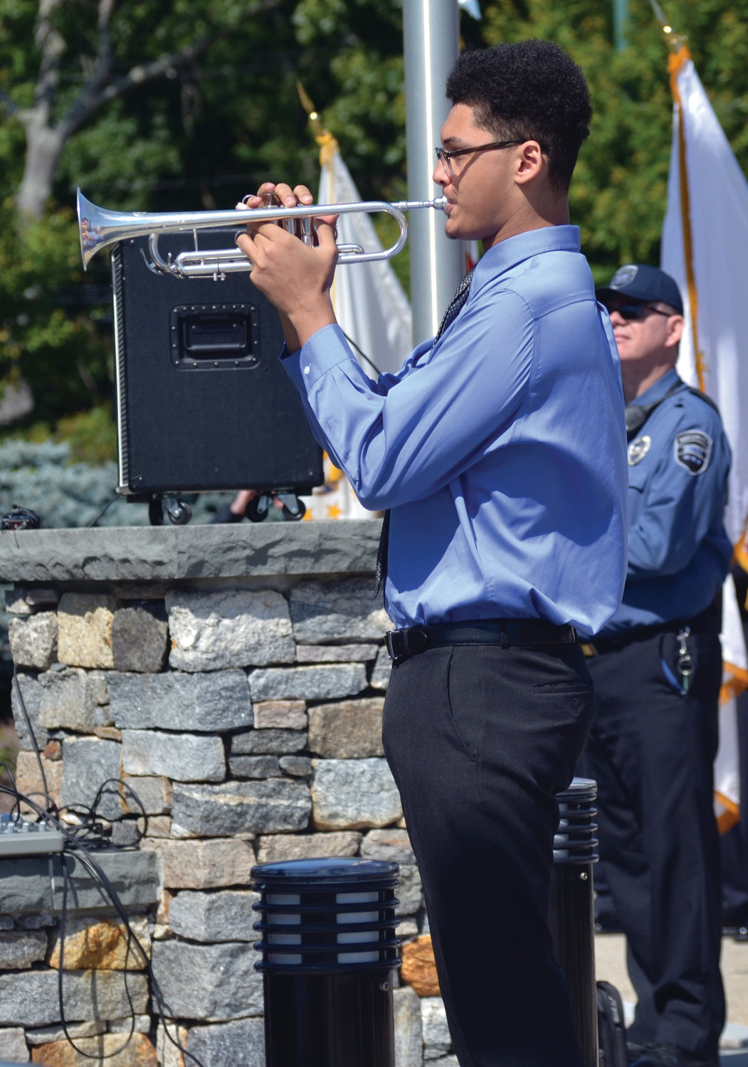A SOMBER NOTE: West Warwick High School senior Kanon Richards played taps as the American and NEIT flags were lowered to half-mast.