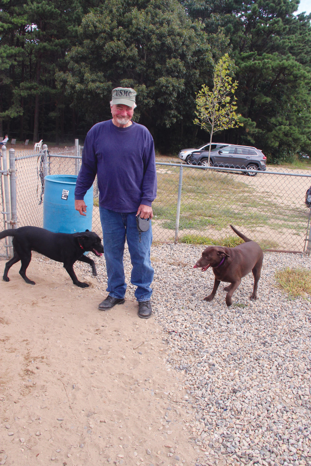 READY TO RUN: Arthur Colvin with two of the three labs he brought to the dog park Sunday morning. The black one is named Dog and the chestnut is Girl, he explained with a laugh.