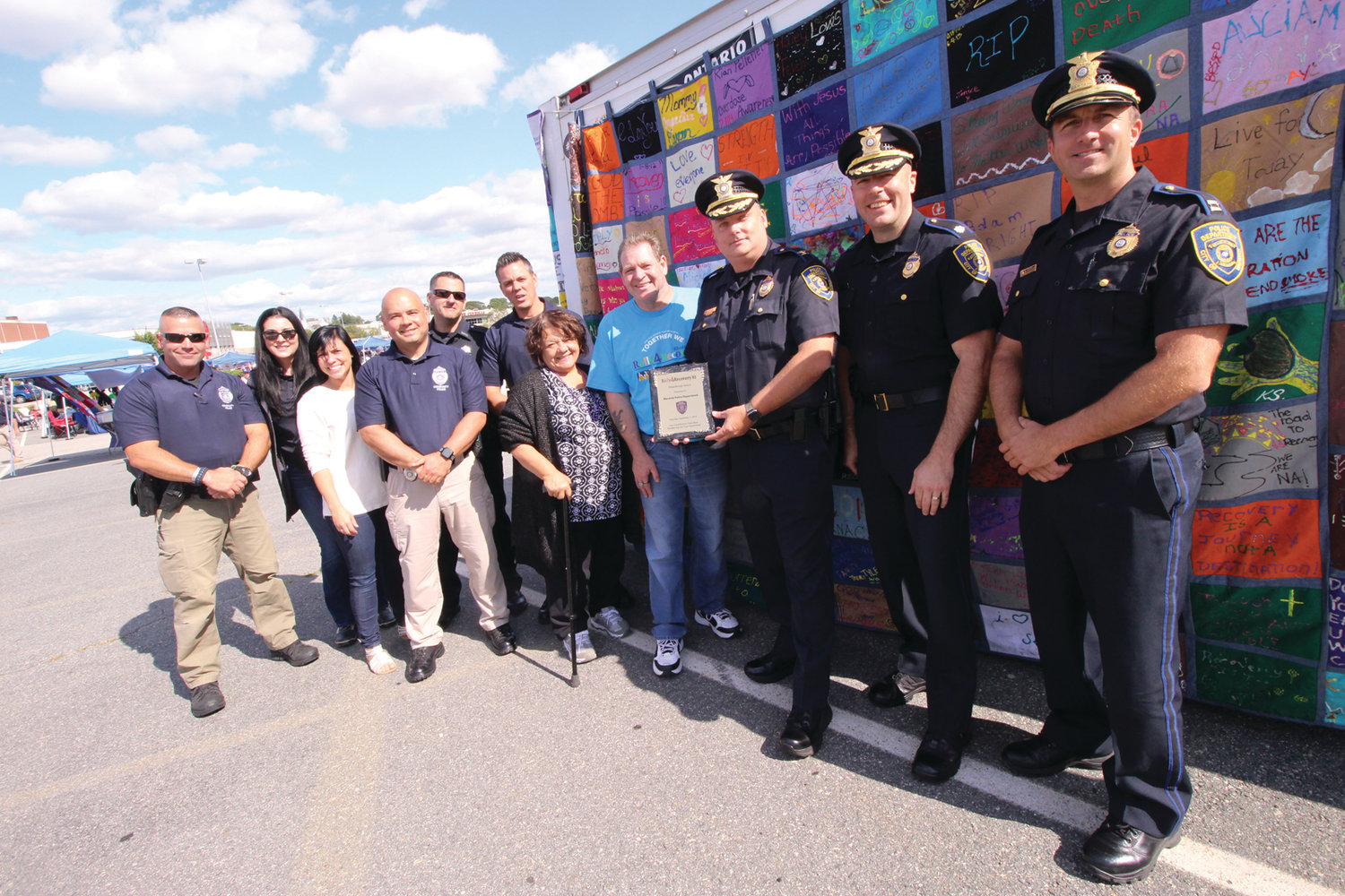 A COMMUNITY EFFORT: With a quilt honoring those in recovery as a backdrop, Col. Rich Rathbun displays the award presented Warwick Police on behalf of the Rally 4 Recovery with Rally 4 Recovery president George O'Toole, members of the department and council members Donna Travis and Steve McAllister.
