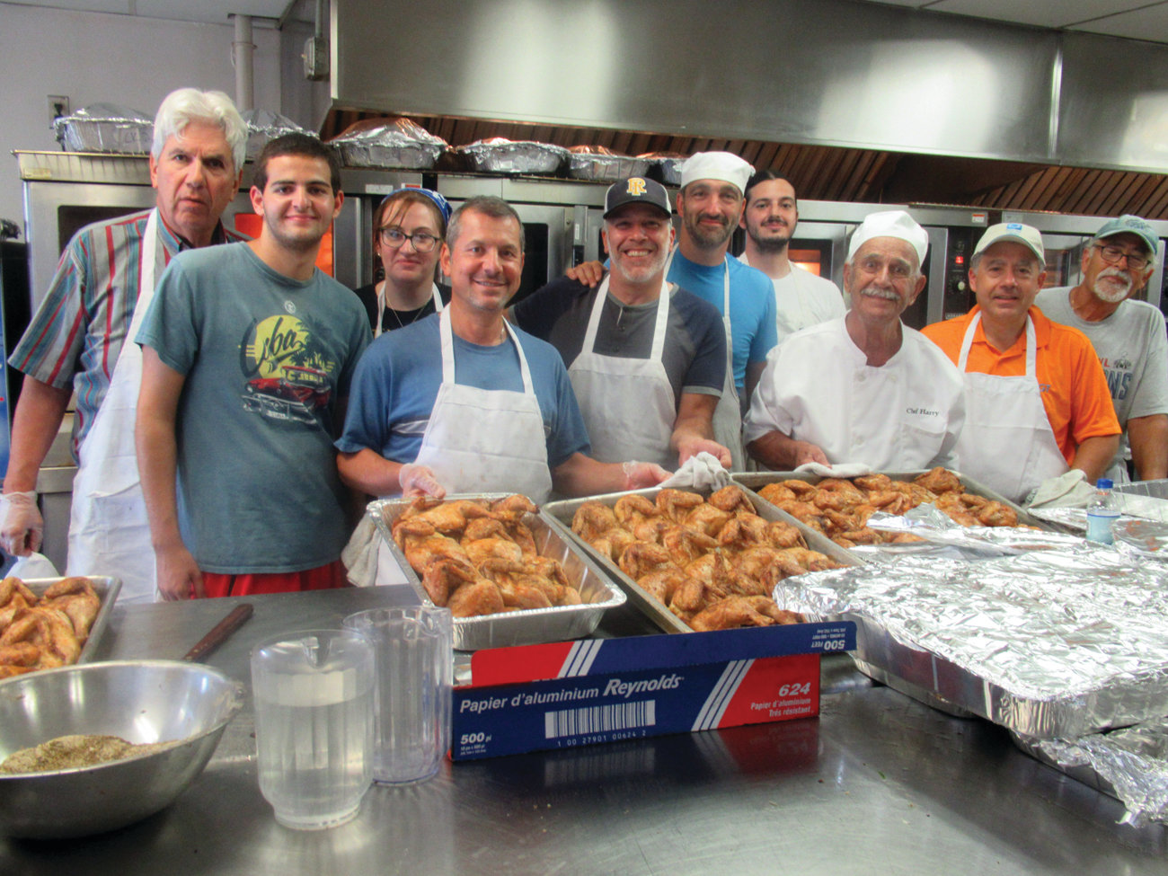 BEBLENIS' BUDDIES: Head chef Harry Bablenis is surrounded by the cooks who turned out roast chicken, lamb and souvlaki during the three-day Cranston Greek Festival.