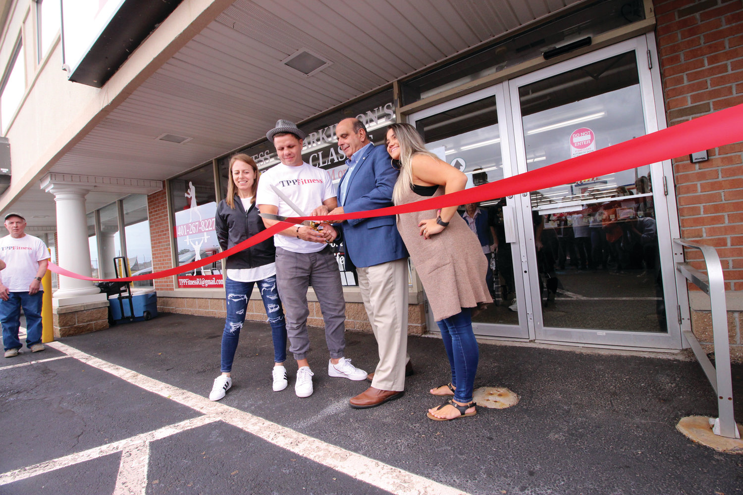 OFFICIAL WELCOME: Joined by TPP Fitness founder Rich Gingras, coach and trainer Paula Silva (left) and assistant manager Larissa Jungermann, Mayor Joseph Solomon snipped the ribbon to open the gym at Airport Plaza.
