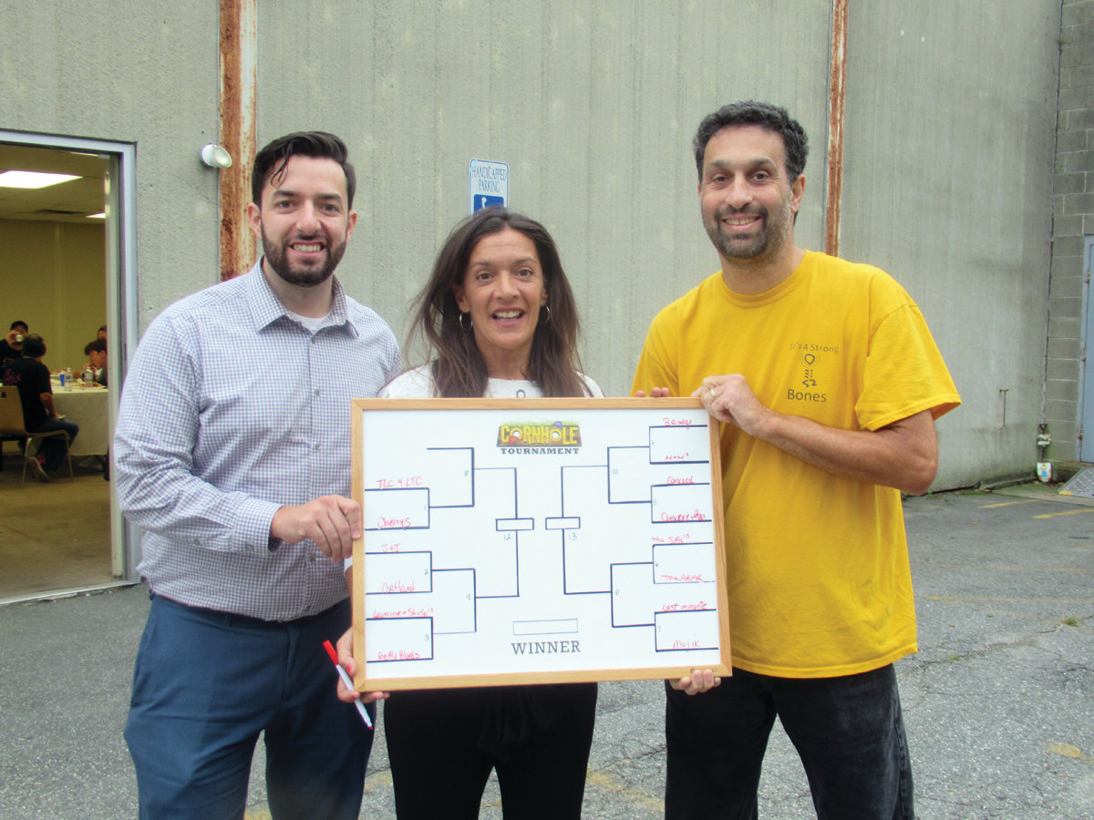 BRACKET BOARD: Keri Salinger, center, holds the official bracket board for the Cornhole Elimination Tournament. She is joined by her son Justin Salinger, left, and committee member Mark Berger.