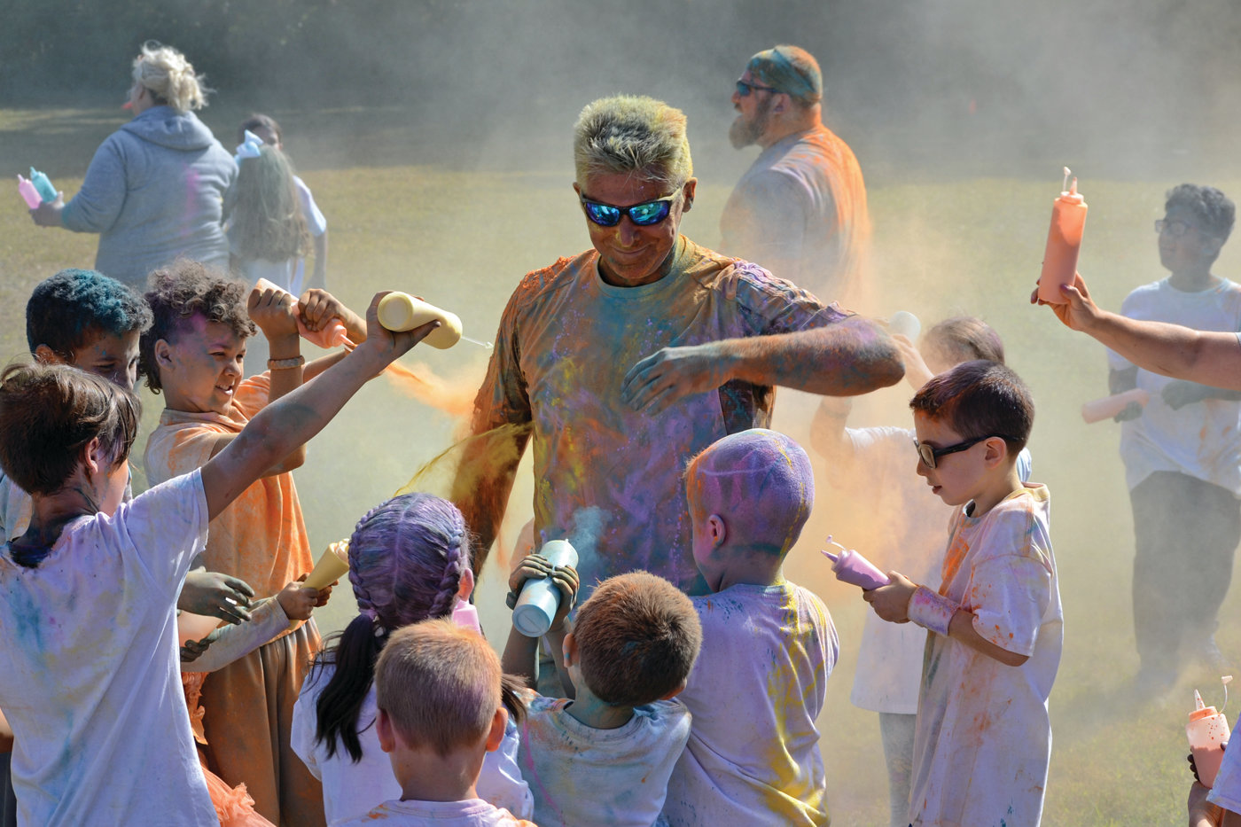 SHOWING HIS TRUE COLORS: Hoxsie Elementary Principal Gary McCoombs smiles as he relents to students dumping the remaining color chalk onto him at the end of the school's second annual Color Fun Run on Saturday, which raised over $8,000 for the school's PTO.