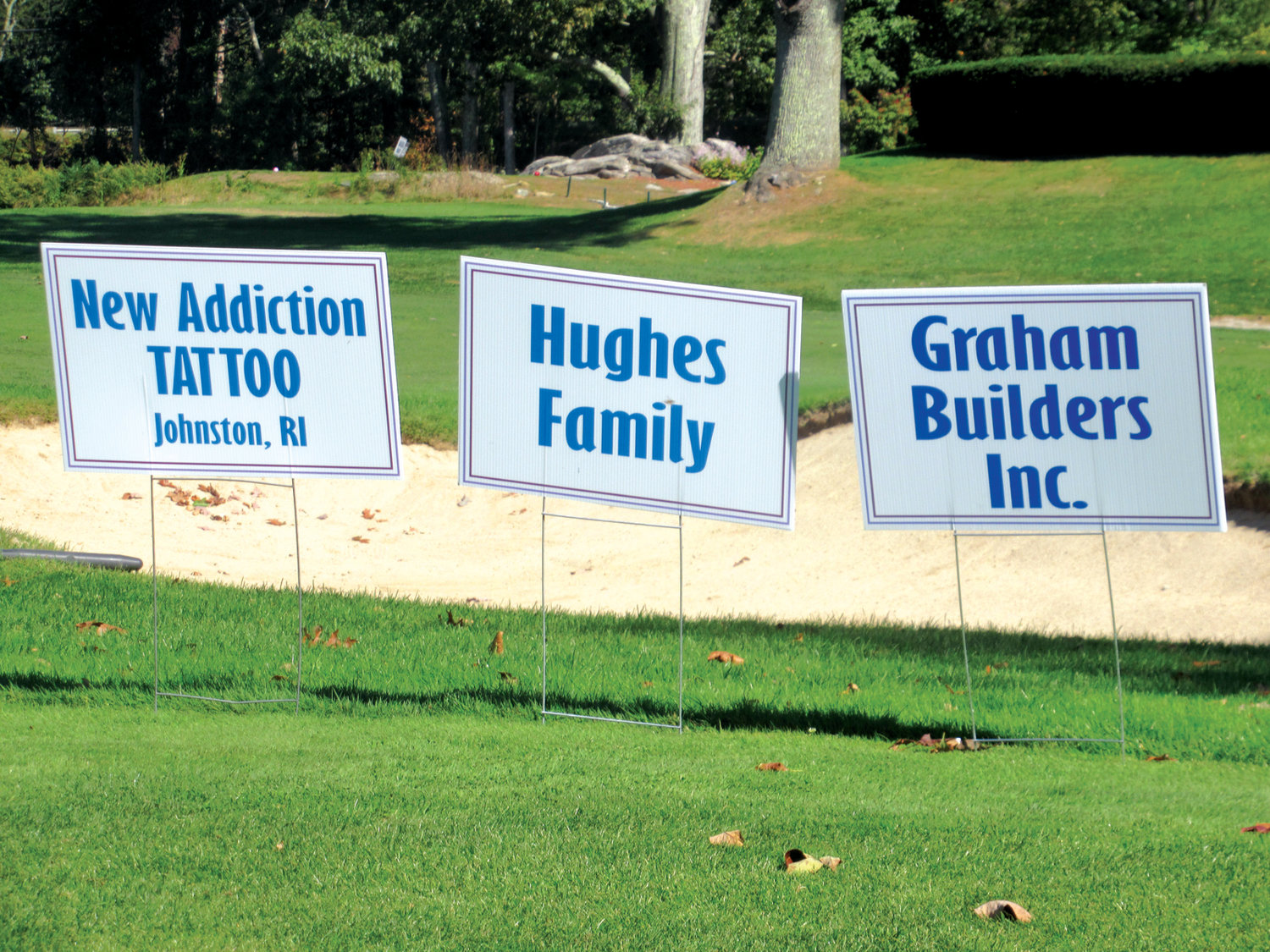 SPECIAL SIGNS: Memorial and business signs such as the ones above helped make Sunday's 5th Annual JMCE Memorial Golf Tournament a smashing success.