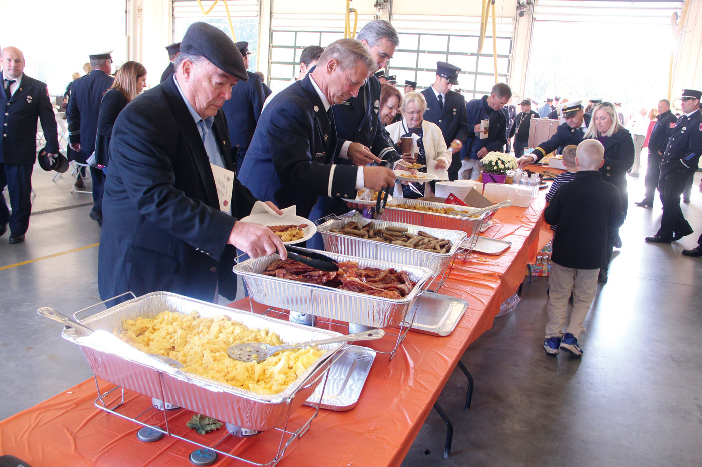 BREAKFAST LINE: Those attending the ceremony were treated to breakfast that was served on the floor of Station One in Apponaug.