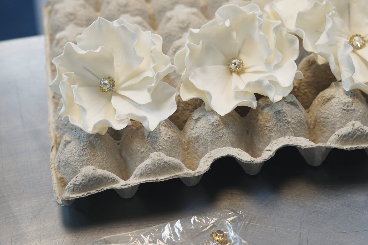 CREATIVE PURSUIT: Intricate, jewel-adorned flowers await one of Queen B's signature custom wedding cakes on Sept. 13.
