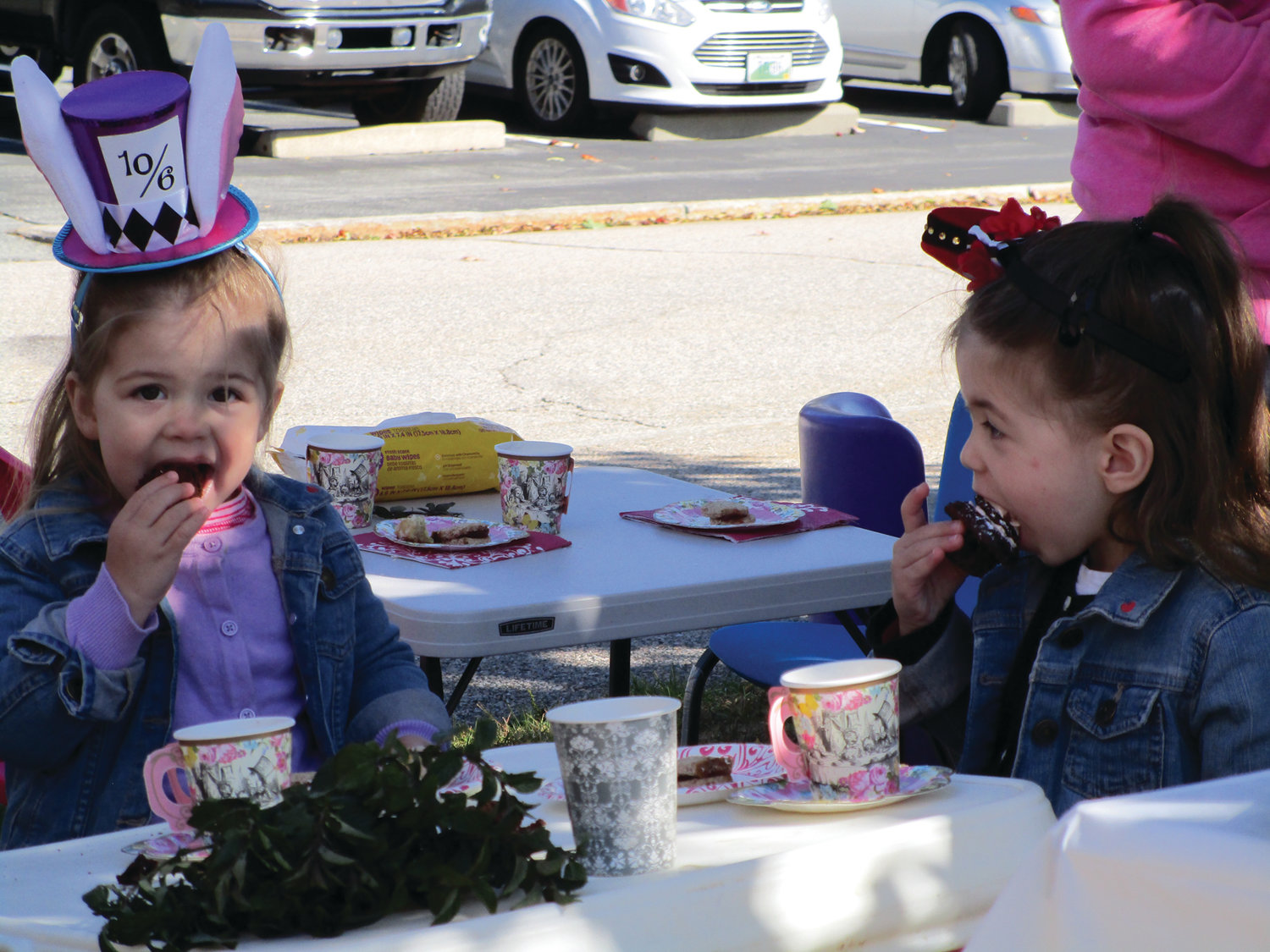SOMETHING SWEET: Ava and Olivia Coray enjoy cupcakes during Saturday morning's tea party at the Pawtuxet Village Farmers Market.