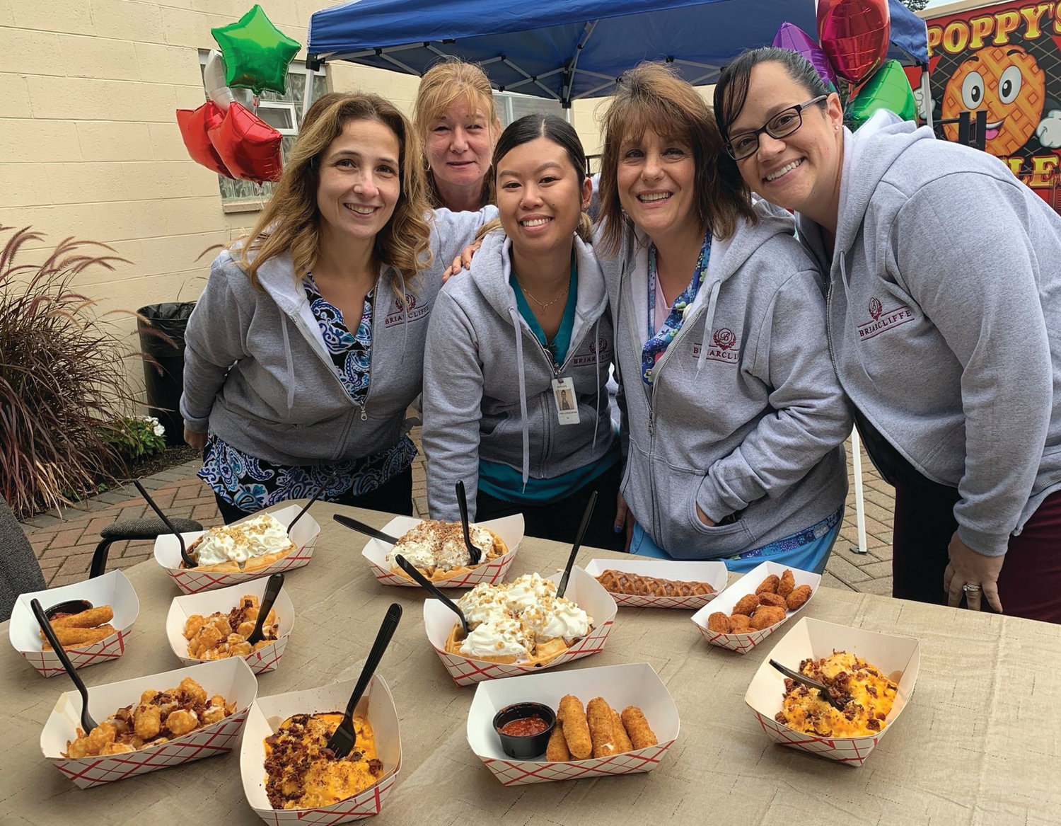 MOUTH-WATERING MUNCHIES: Briarcliffe nurses Jonna Matos, Lorna Parrillo, Linda Laungasoupom, Deborah Petronelli and Beth Brosnahan enjoy a lighter moment in front of the Poppy's Waffle truck while waiting to sample the many unique foods that were featured during the recent Nurses Appreciation Day Luncheon.
