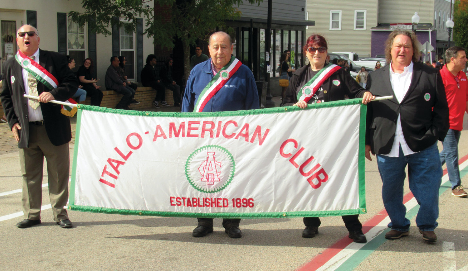 LOCAL LINK: Johnston residents Carmine DeRobbio, second left, and Linda Folcarelli were among the people who proudly carried the Italo-American Club banner in Sunday's Columbus Day Parade on Federal Hill.