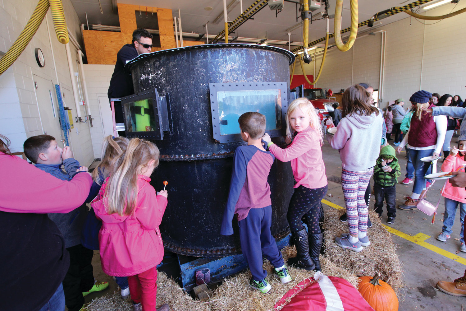 IN THERE SOMEWHERE: Kids gather at the windows of a tank where a firefighter demonstrated diving equipment and maneuvers.