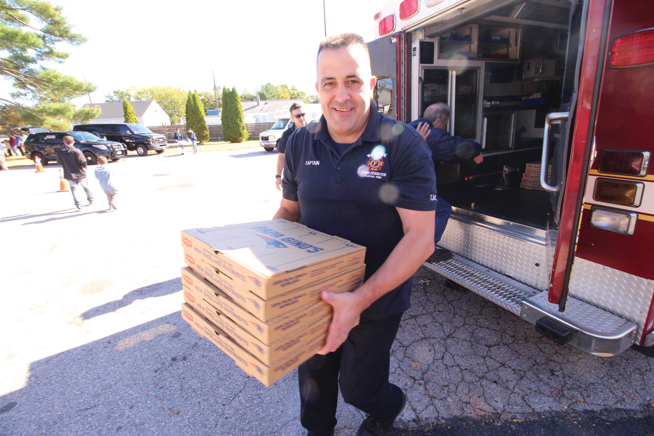 PIZZA TO THE RESCUE: Captain Bill Wilson helps unload pizza after a rescue make a run to Papa Gino's.