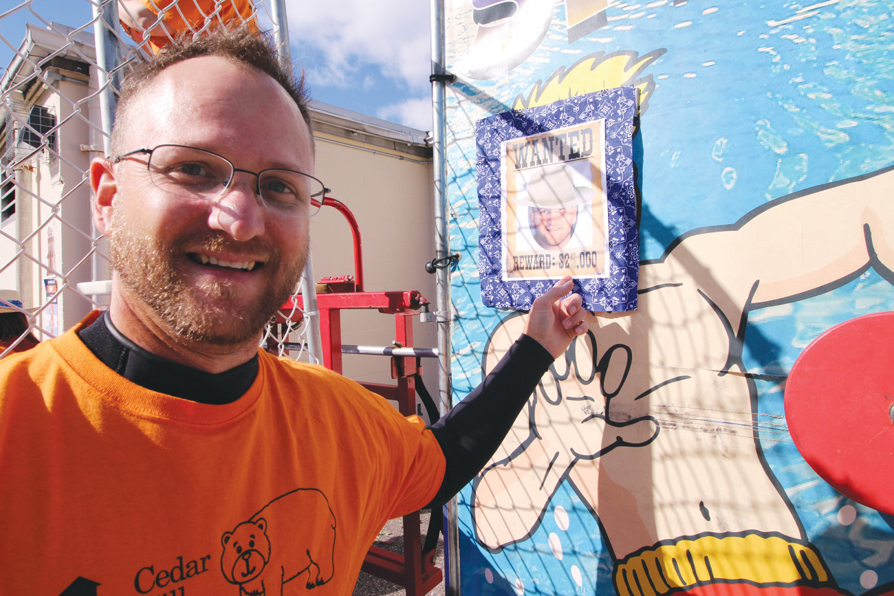 WANTED WET: A dry Cedar Hill School Principal Frederick Schweizer beside the dunk tank and his wanted poster.