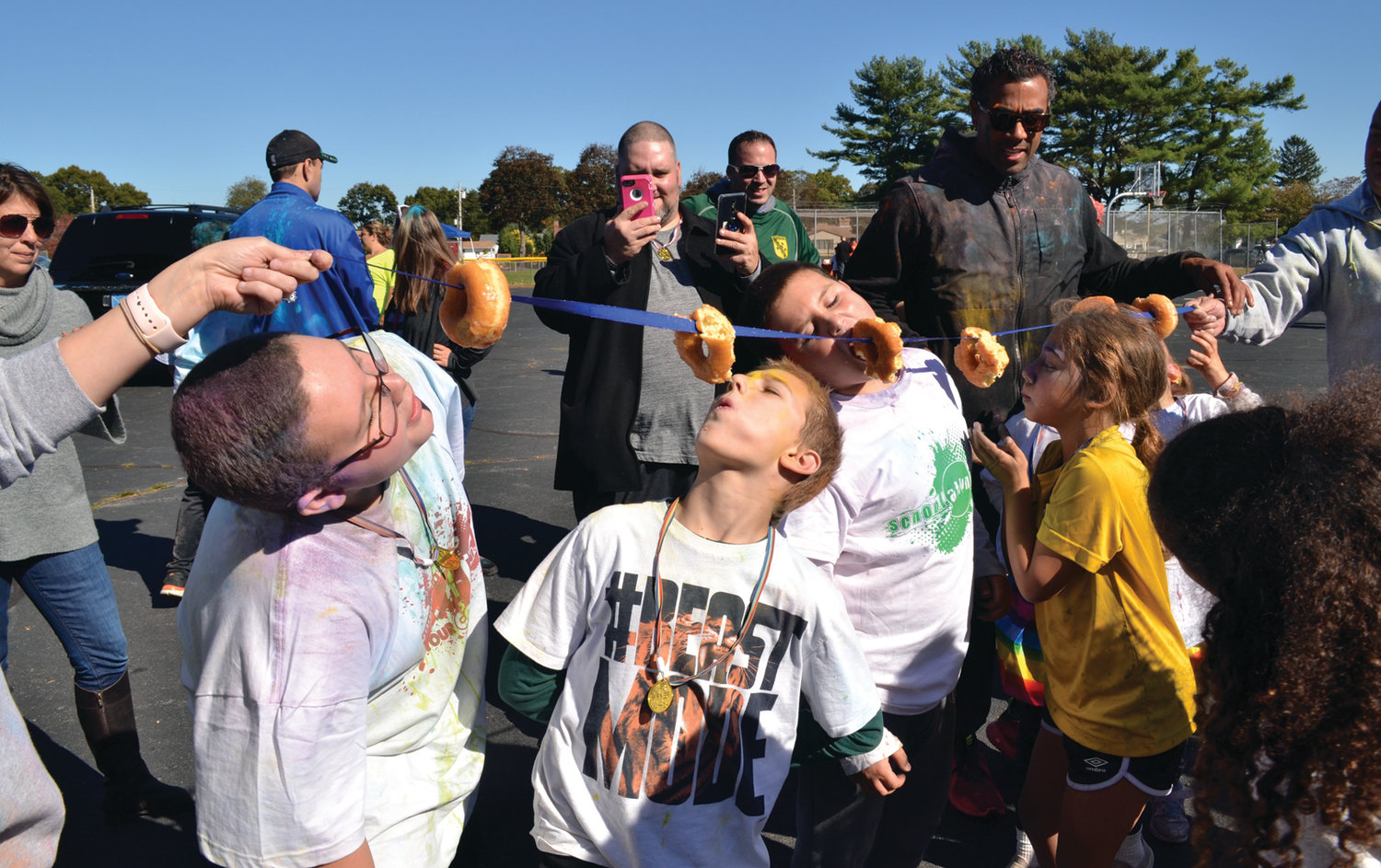 A BITE OF FUN: Students took part in a few rounds of the donut-eating contest during Saturday's Color Run, as adults at each end held a string off of which participants had to eat without using their hands.