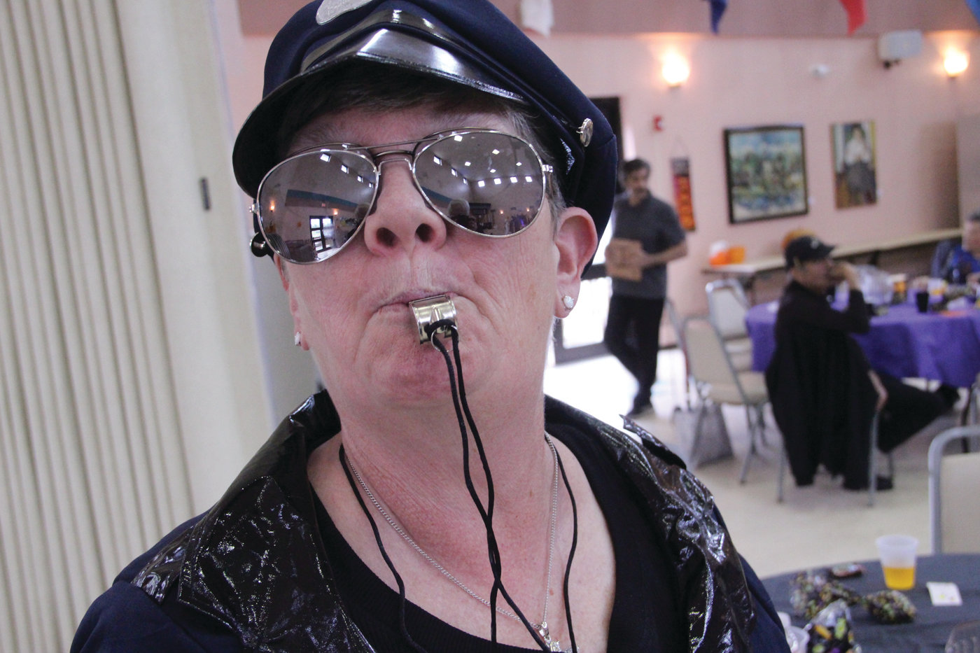 "BLOWING THE WHISTLE ON HALLOWEEN: She didn't get to use her handcuffs or nightstick, but Maureen Sheats, who wore the badge ""Rita Dem Rites,"" willingly sounded her approval as fellow members took to the dance floor for Thursday's Pilgrim Senior Center Halloween party."