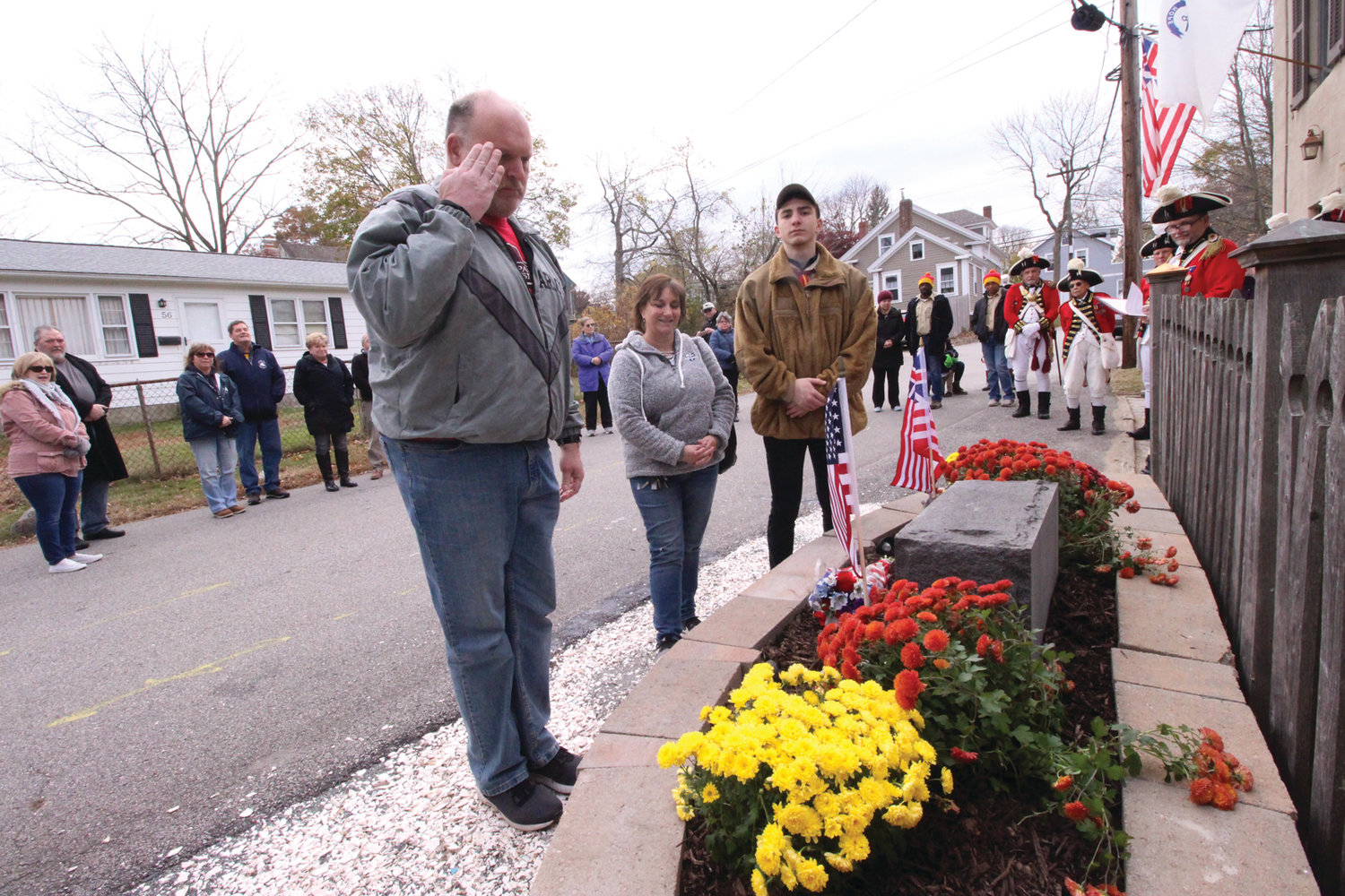 AT DEDICATION: James Loffler, his wife and his son Nicholas stand at the memorial garden at the Pawtuxet Rangers Armory. Nicholas built the garden as his Eagle Scout project.