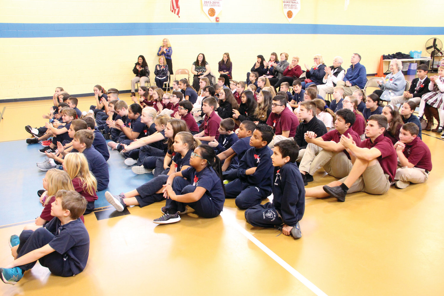 ATTENTIVE AUDIENCE: St. Rose of Lima faculty and students observed Veterans Day on Thursday listening to family members of their classmates describe their experiences serving this country.