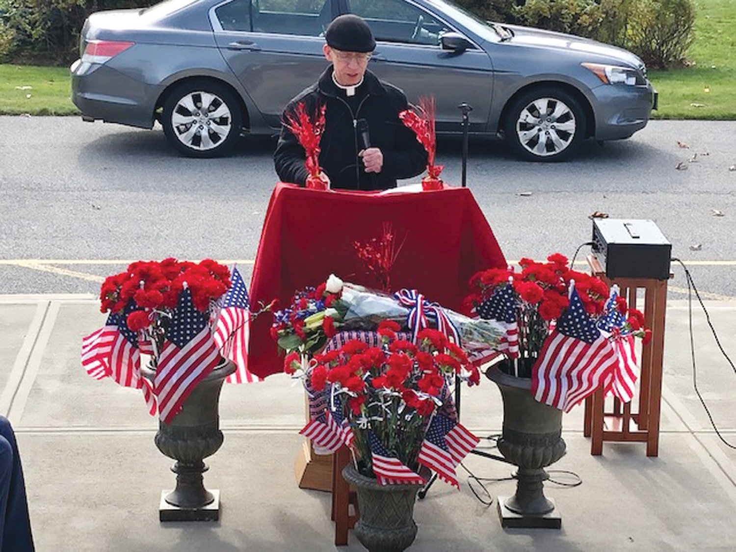 REMEMBERING VETERANS: Father Andrew Messina read the names of veterans from the steps of Saints Rose and Clement Church following Mass on Sunday.