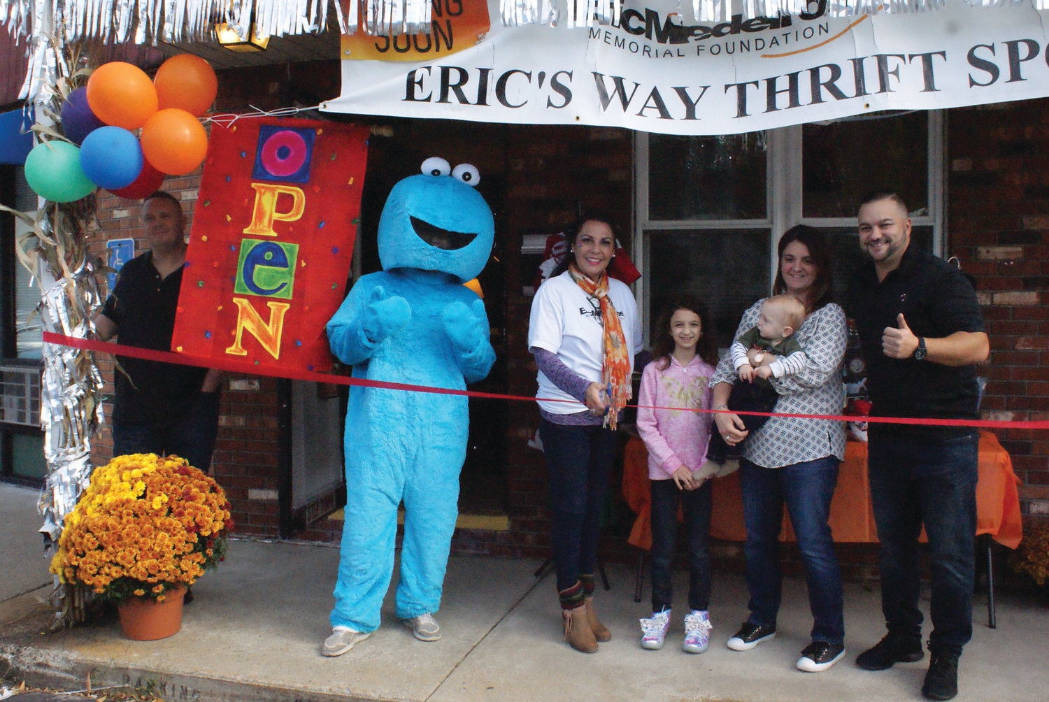 NEW BUSINESS: Eric's Way Thrift Spot has opened at 471 Atwood Ave. and celebrated its grand opening on Oct. 26. The store sells new and gently used items to benefit the Eric Medeiros Memorial Foundation. Pictured at the ribbon-cutting ceremony are, from left, Matt Adams, Cookie Monster (Philip Page), owner Anna Casador-Saccoccio, Abby Bober, Benjamin Adams, Jeannette Saccoccio and Ward 4 City Councilman Ed Brady.
