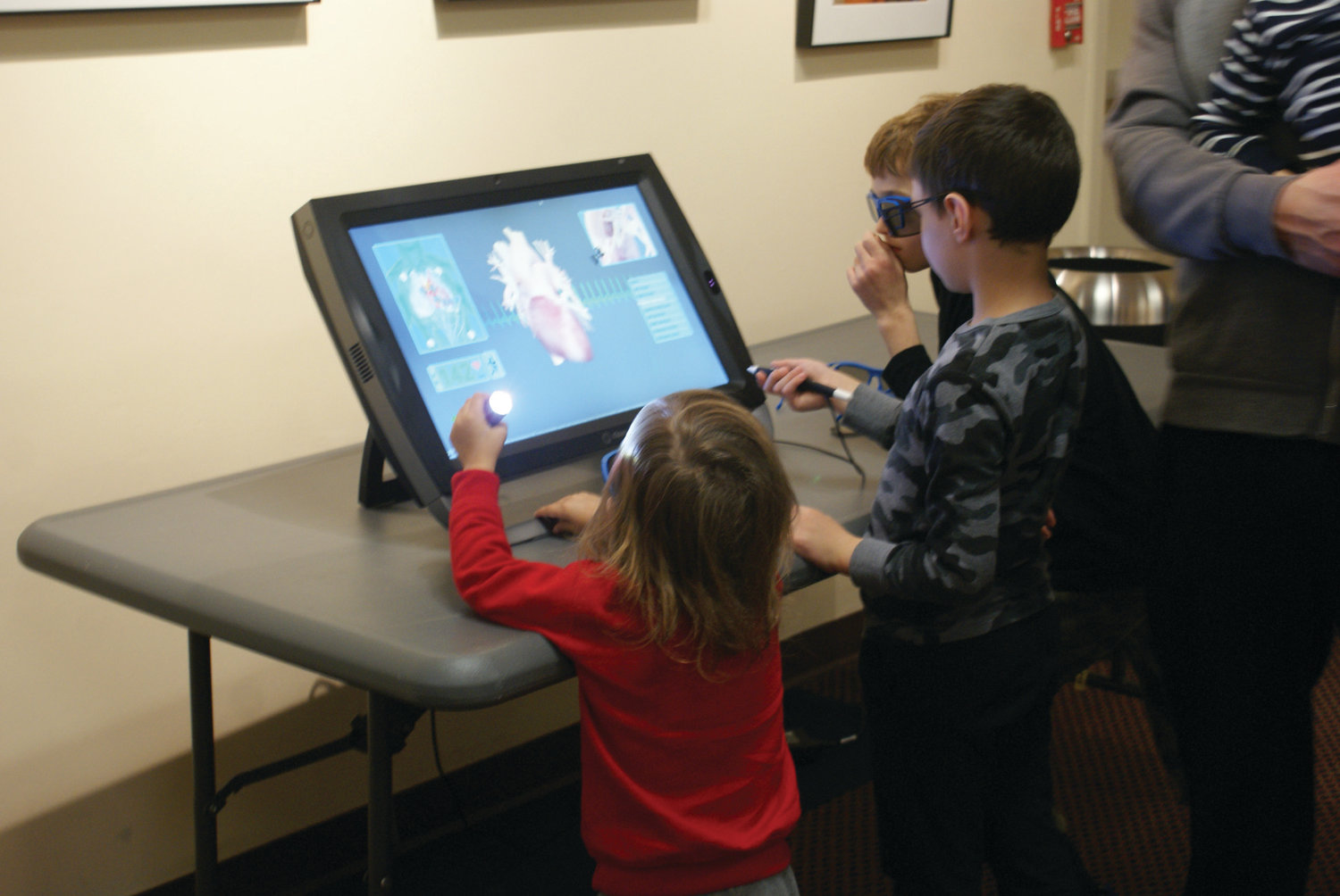 3D STATION: Looking at a three-dimensional view of a beating heart during X-Ray Vision Family Fun Day were 3-year-old Henry Bartos, 6-year-old Michael Yingling and 8-year-old Asher Germanowski.