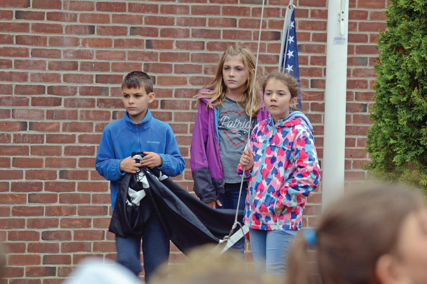 FLAG CREW: Aidan Flanagan, Madeline Scott and Lily Smiley were the students tasked with raising the flag to begin the day's ceremony.