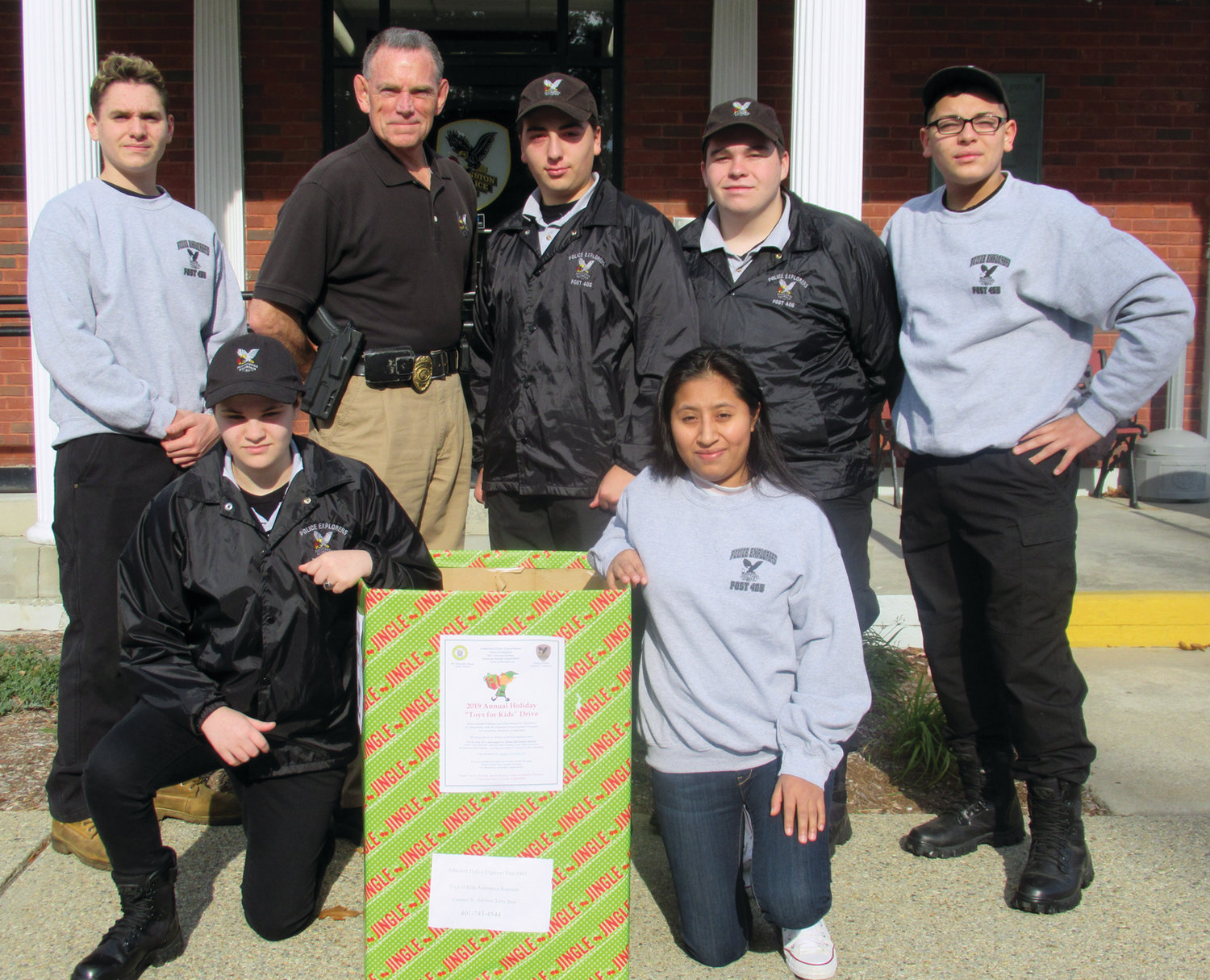 "EXPLORER ELVES: Among the many members of the Johnston Police Explorers Post 405 taking part in the annual ""Toys for Kids Drive"" are, kneeling from left, Jessica Council and Elvira Larios; and top from left, Explorers Benjamin Barnier, JPD Major Thomas H. Dolan, Kaleb Mendez, Philip Thompson and Michael Camarena."