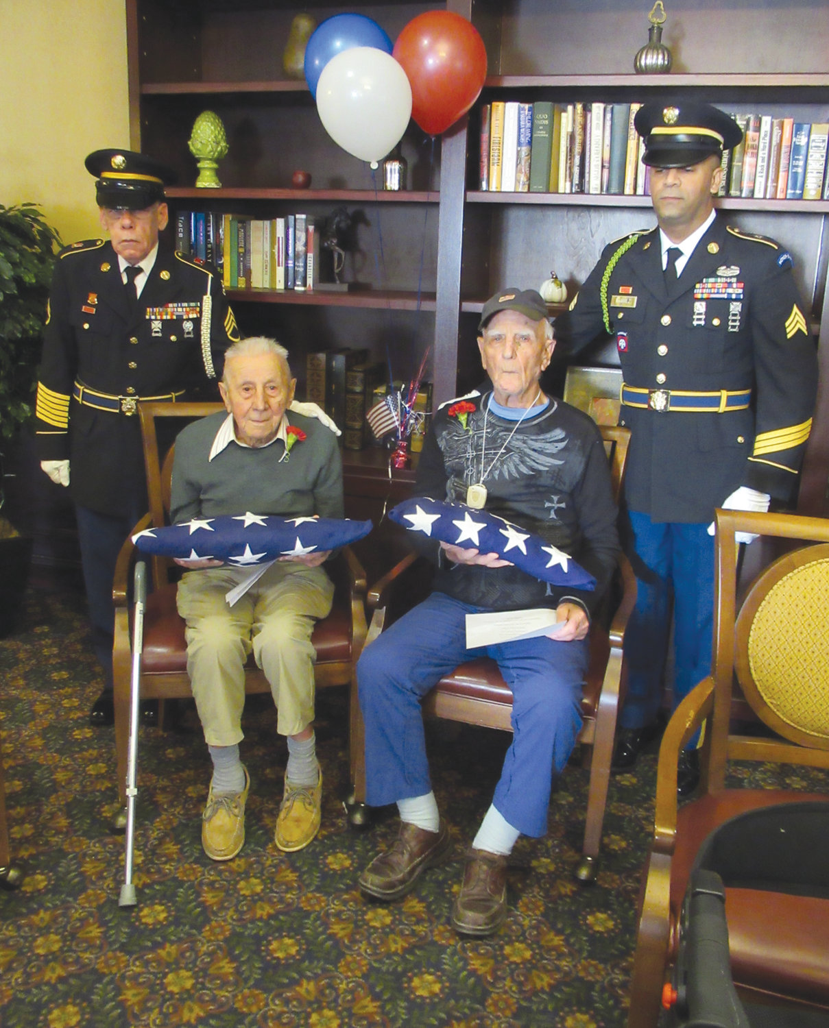 SPECIAL SALUTE: U.S. Army Staff Sgt. Mark McGrath, standing left, and Sgt. Richard Ramirez, standing right, join Nazareth Piccirilli, seated left, and George Costa, seated right, with an American flag in honor of being the oldest veterans living at The Bridge at Cherry Hill.