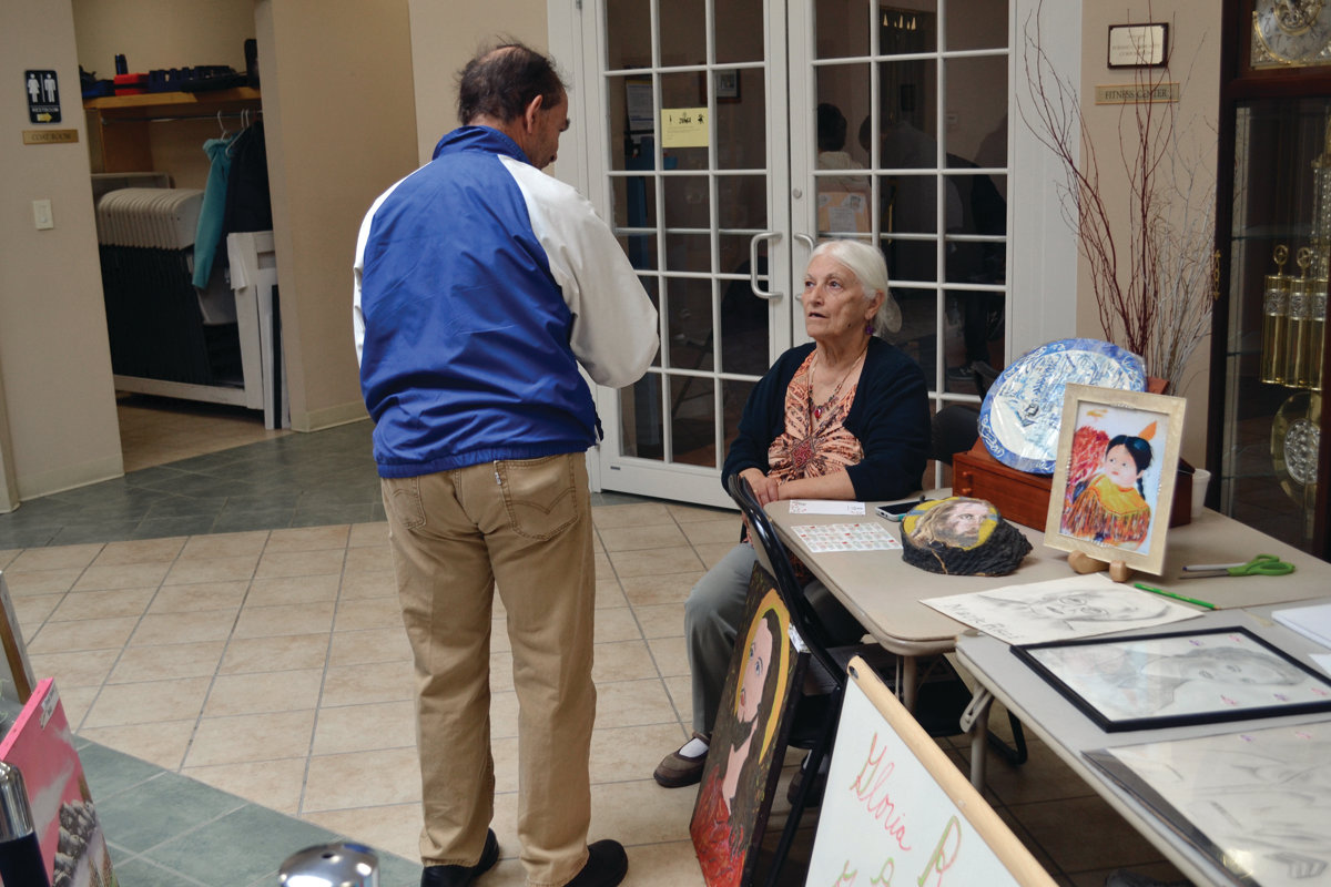 TALKING SHOP: Gloria Renzi chats with a patron at the Johnston Senior Center last Thursday. Several folks filed through her gallery, looking over all of the work she had available for purchase.