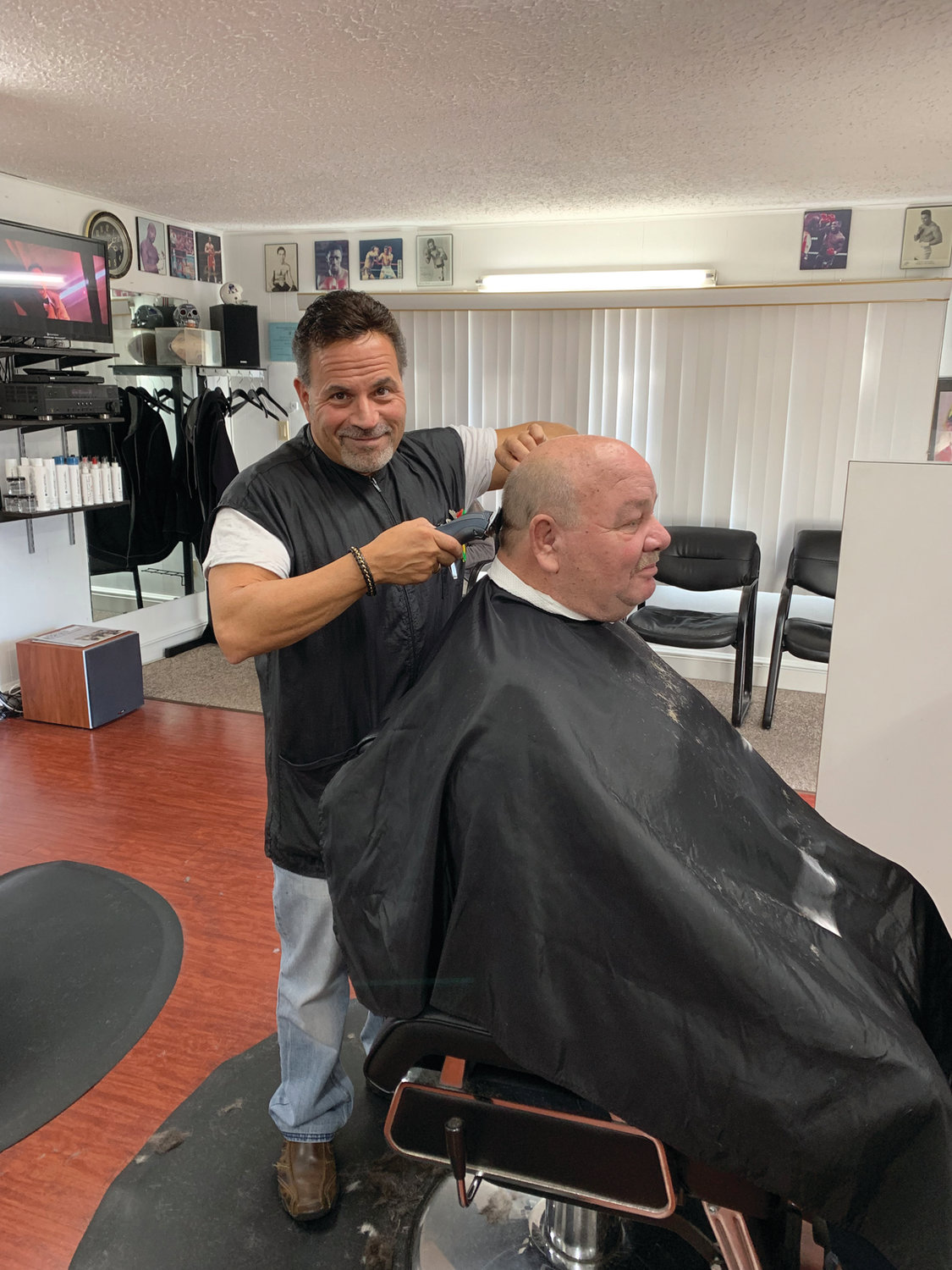 Dave Picozzi catches the lens of the camera as he cuts the hair of longtime customer Roy Kelvey.  Roy and Dave have known each other for over 30 years when Dave first started cutting Roy's hair. Loyalty and longevity are two things David's Greenwood Barbershop values and has worked hard for.