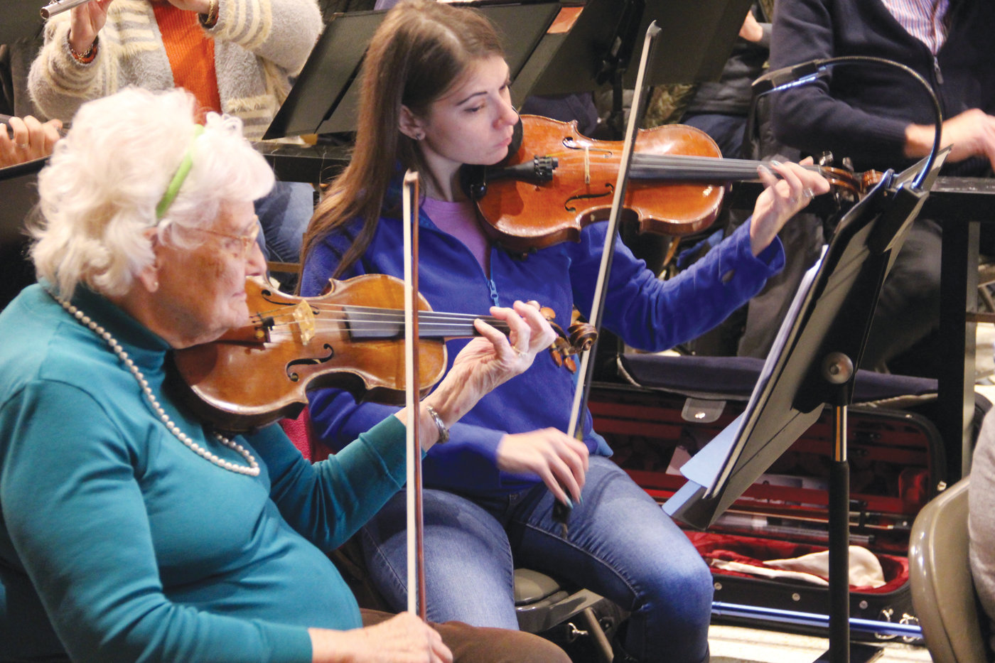 STRINGS THAT SING: Gerri LaJoie and Mari Ingesson, members of the Ocean State Pops Orchestra, in a recent rehearsal for the upcoming holiday pops concert.