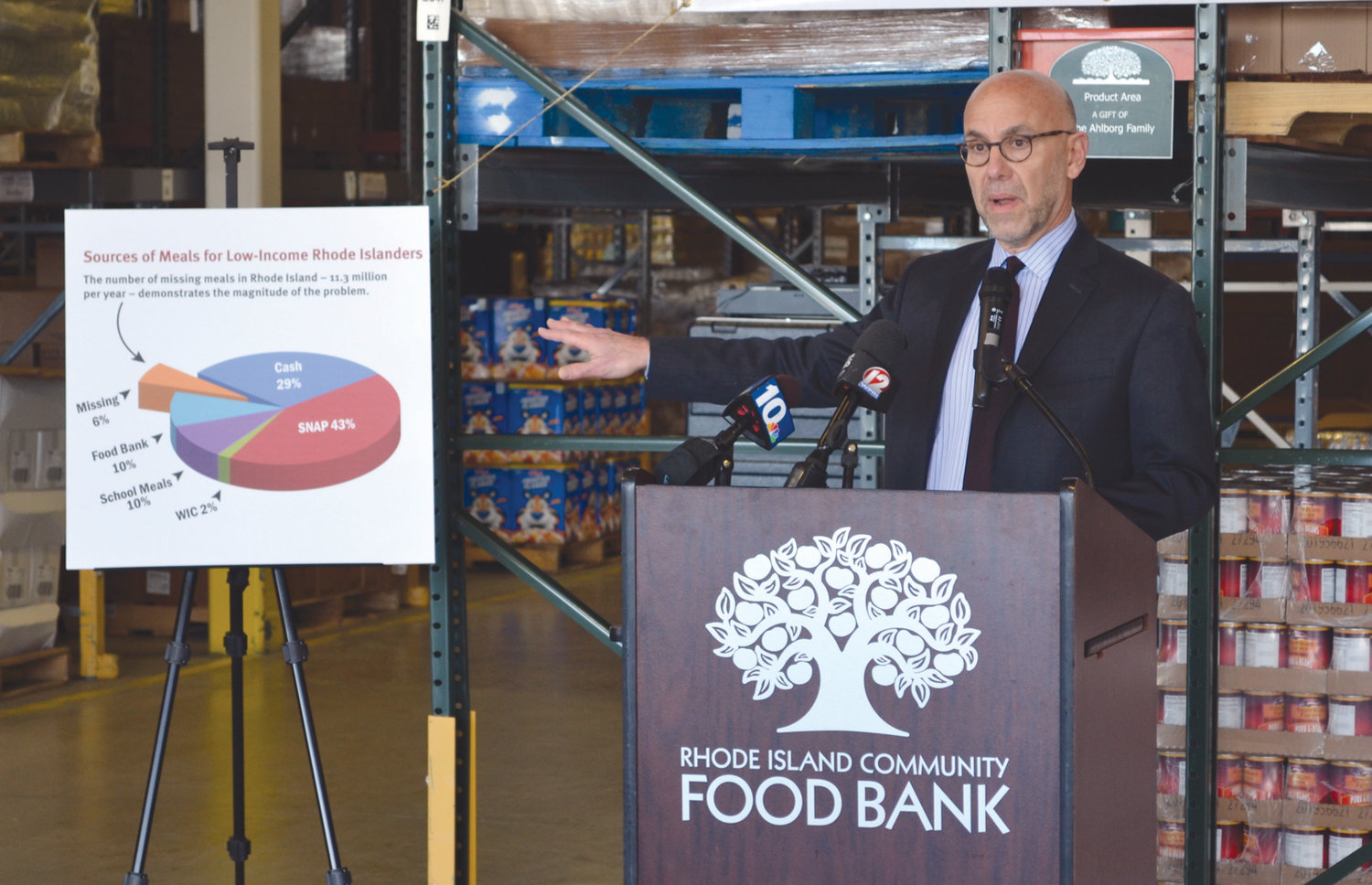 SHOWING THE NUMBERS: Rhode Island Community Food Bank CEO Andrew Schiff gestures to a pie chart showing that low-income Ocean State residents miss out on 11.3 million meals every year.