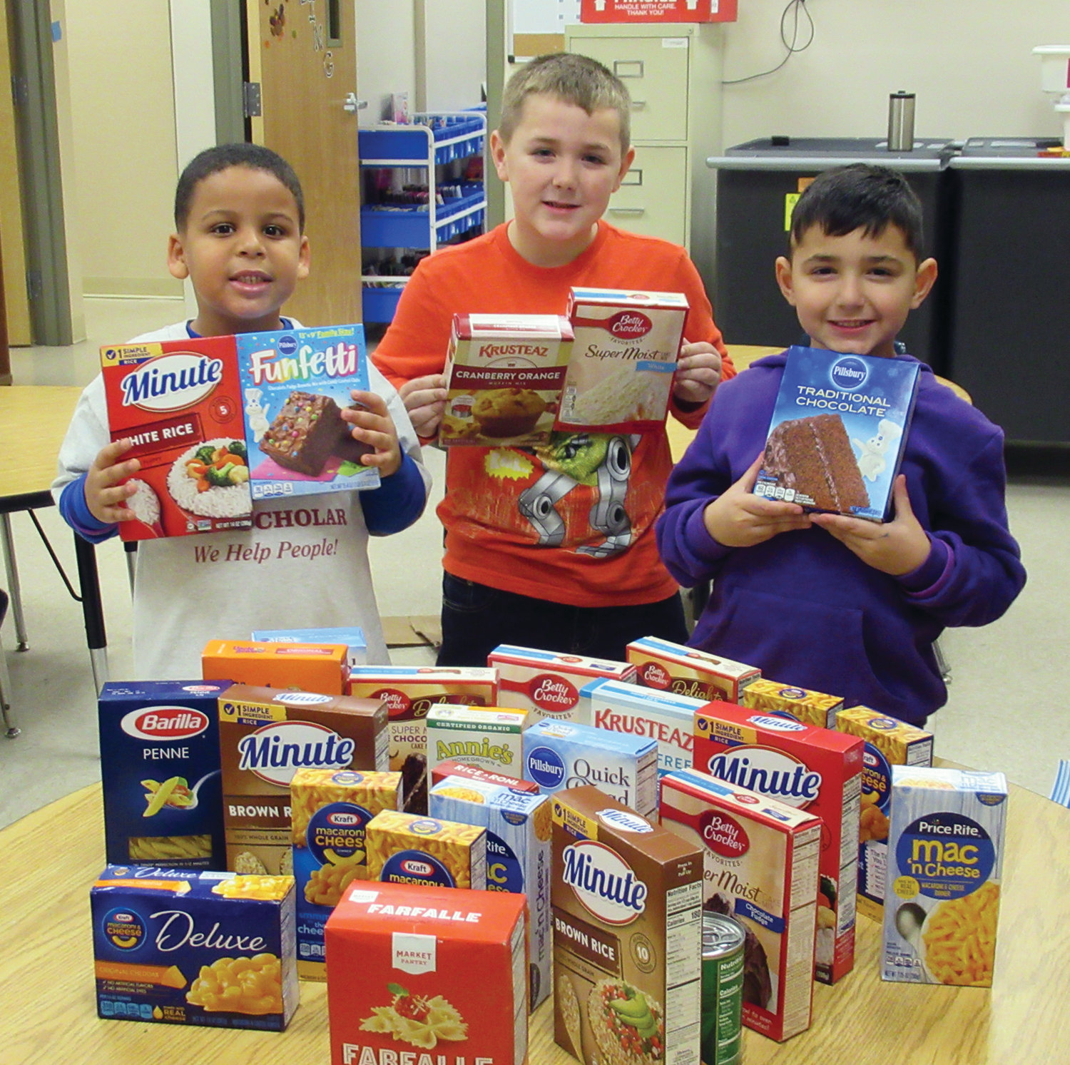 CLASSIC COLLECTORS: ECC students Javier Santana, Marshall Lavoie and Evan Pistocco show off some of the nonperishable foods items the Johnston school collected to help fill the Food Pantry at Thornton Elementary School.