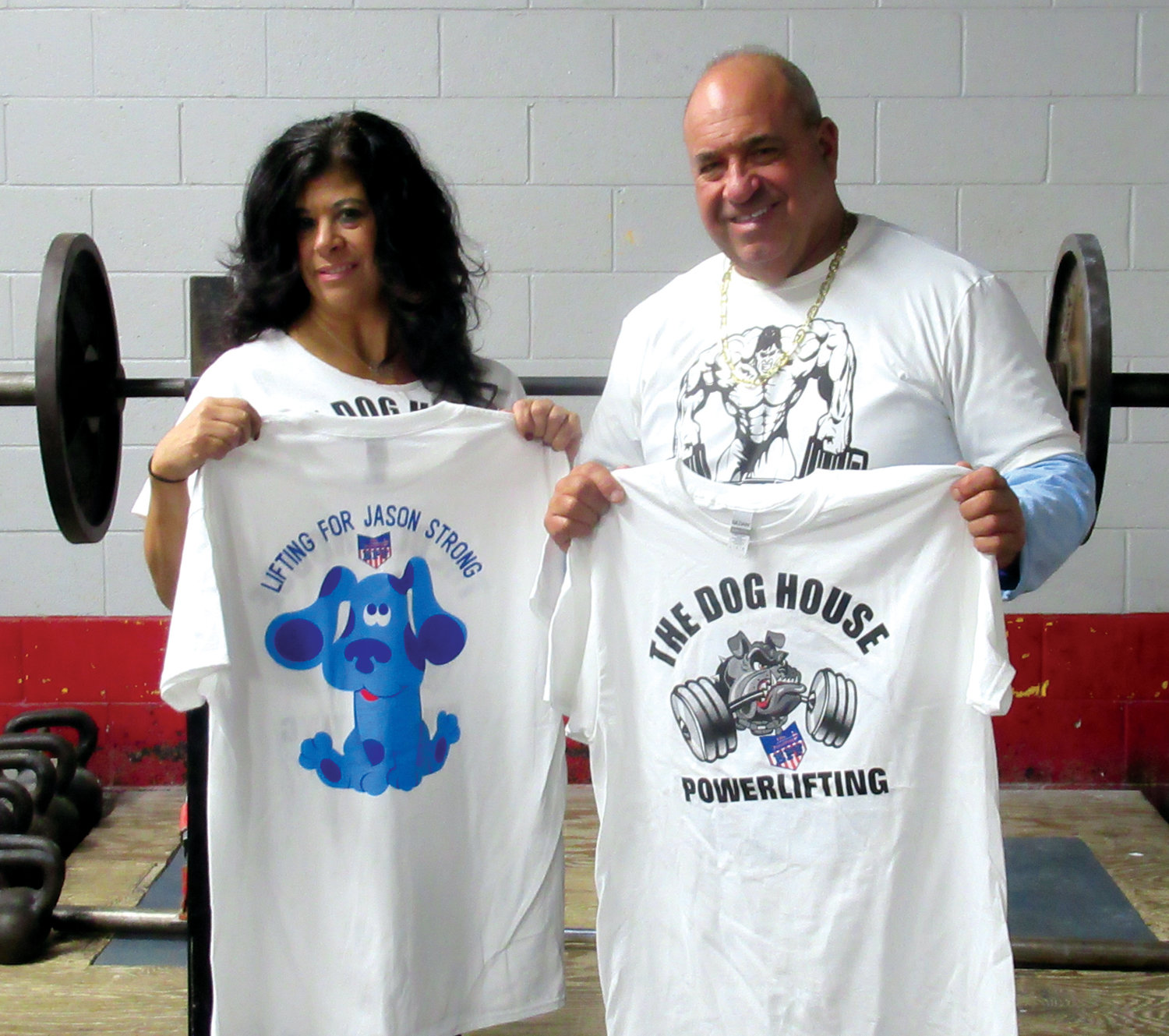 POWER PAIR: Gina Sabitoni-Arakelian and George Lazzareschi are holding the specially designed T-shirt that will be on sale during Saturday's New England Regional Powerlifting Championships in Johnston. Proceeds will help provide Jason Lopes, 15, with his own service dog.