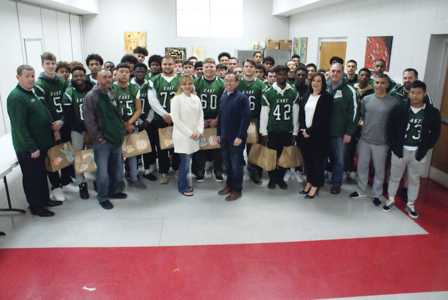 COMMUNITY SPIRIT: Mayor Allan Fung and his wife, Barbara Ann Fenton-Fung, pose with members of the football team from Cranston High School East before they headed out to deliver Thanksgiving meals in the community. The two teams went on to play in the annual Thanksgiving matchup, with West winning the battle 27-0.
