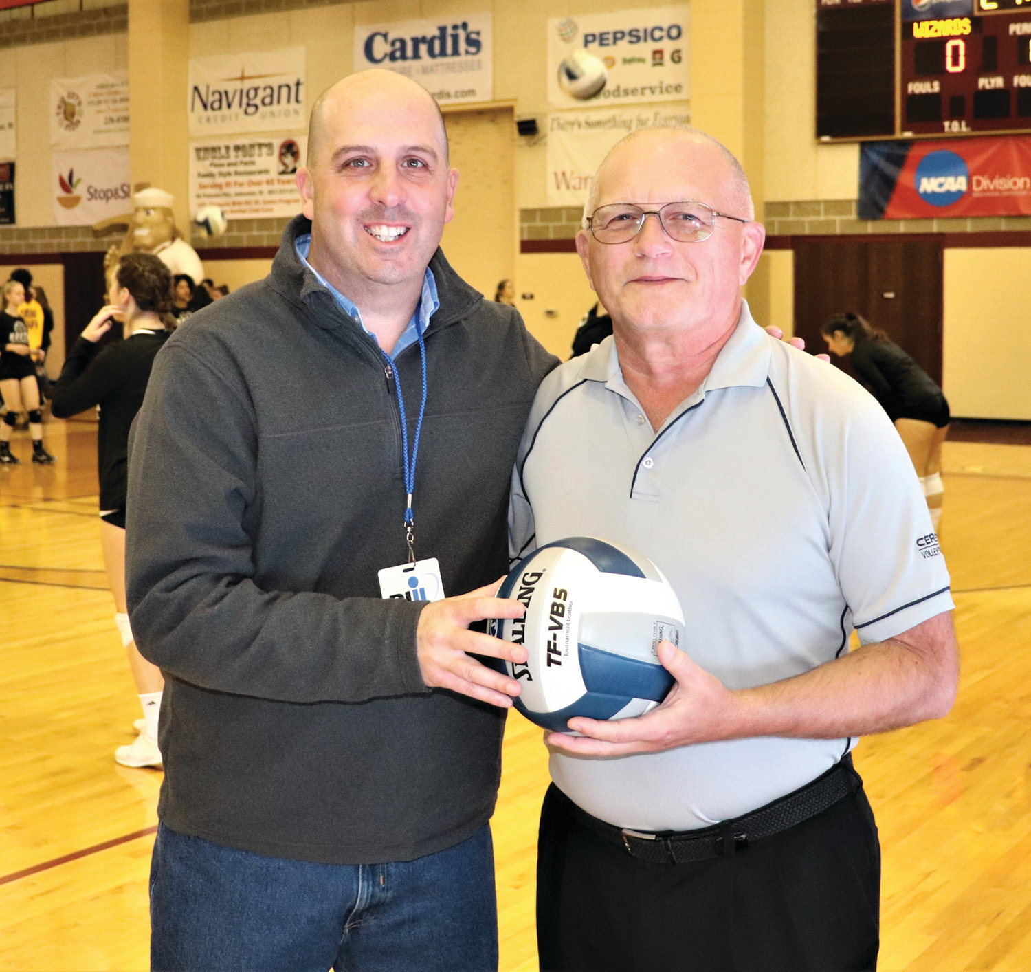 MAN OF HONOR: RIIL Assistant Executive Director Michael Lunney presents Ray DeAngelis with the game ball following his final high school volleyball match.