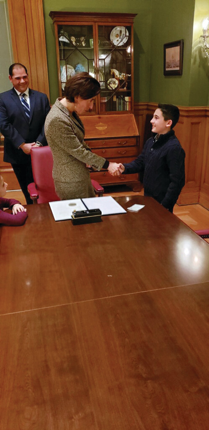 NOTHING BUT SMILES: Johnston 10-year-old Alex Amaral met and shook hands with Gov. Gina Raimondo on Nov. 14 as his father, John, stands in the background. Raimondo would sign a proclamation recognizing World Diabetes Day in the Ocean State.