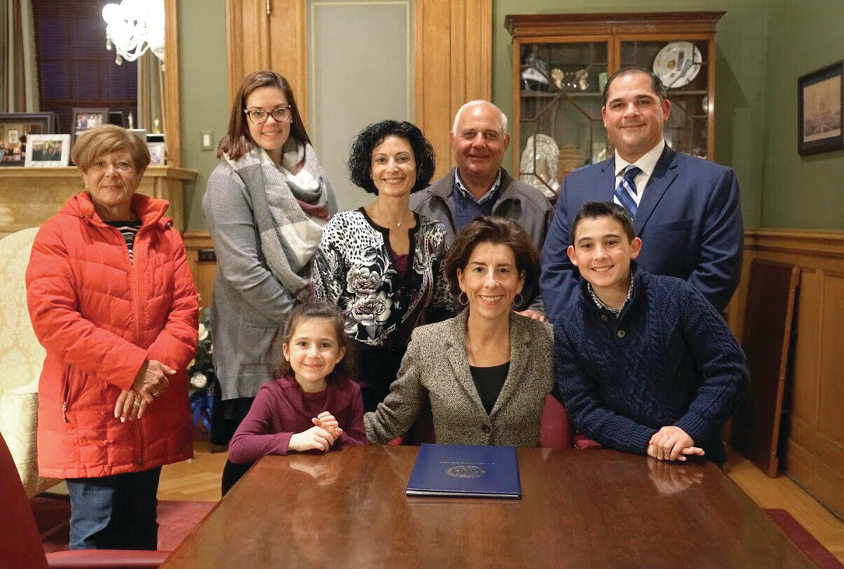 FAMILY TIES: Alex, front right, and his sister, Mia, front left, posed with Gov. Raimondo and their family members during a ceremony on Nov. 14.