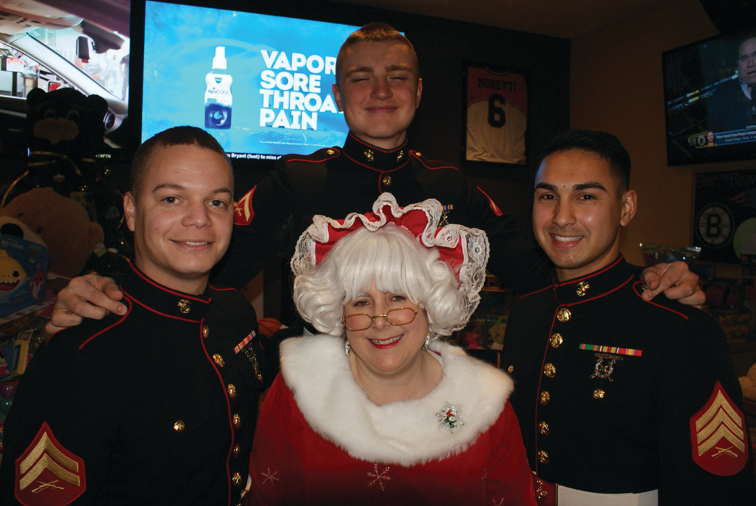 PROUD MARINES: Mrs. Claus shares a moment with Marine Cpl. Jonathan Delgado, Lt. Cpl. Adam Matuzzek and Sgt. Brian Soares.