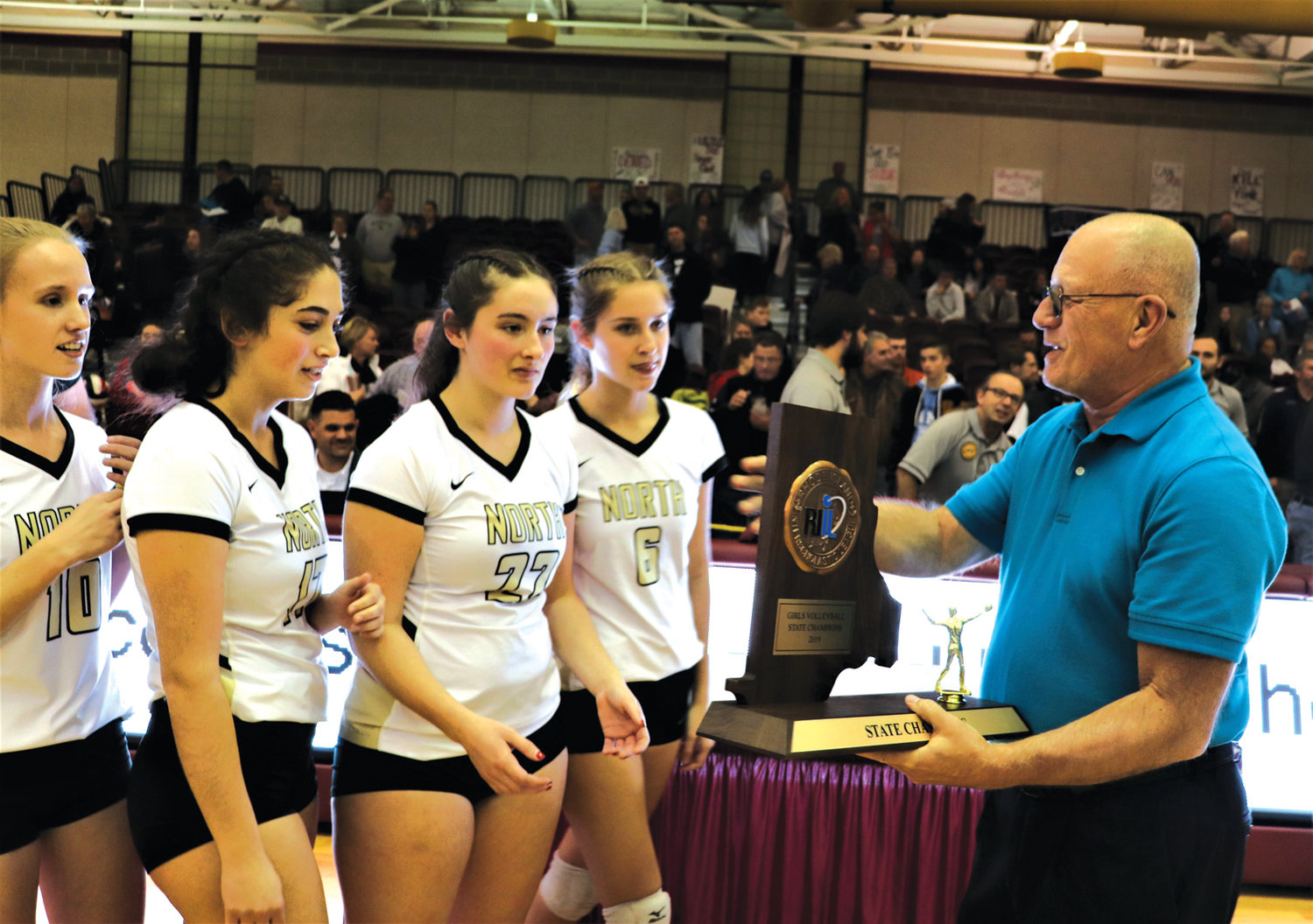 LEAGUE WINNERS: Ray DeAngelis presents the North Kingstown girls volleyball team with the state championship plaque.