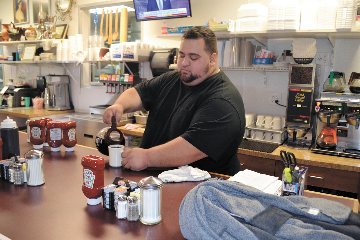 WARM WELCOME: M&M Diner and Pizzeria's Marios Kirios pours a cup of coffee for a customer on Monday afternoon. Kirios said the restaurant will be open from 7 a.m. to 1 p.m. on Christmas Day with a breakfast-only menu.