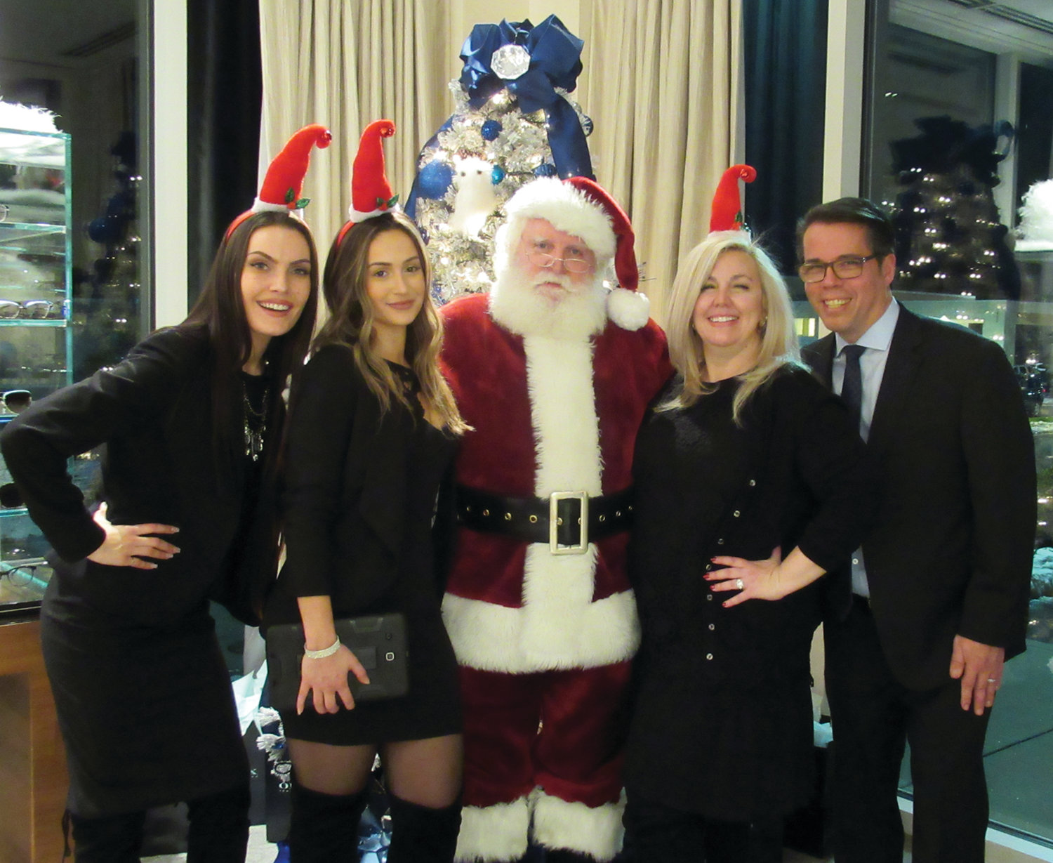 SANTA'S STAFF: Santa Claus made a special appearance during the recent Gucci Extravaganza at OPTX Rhode Island in Johnston and is joined by, from left, Livia Stencel, Jess Santos, CEO Lynne Diamante and Dr. Giulio Diamante.