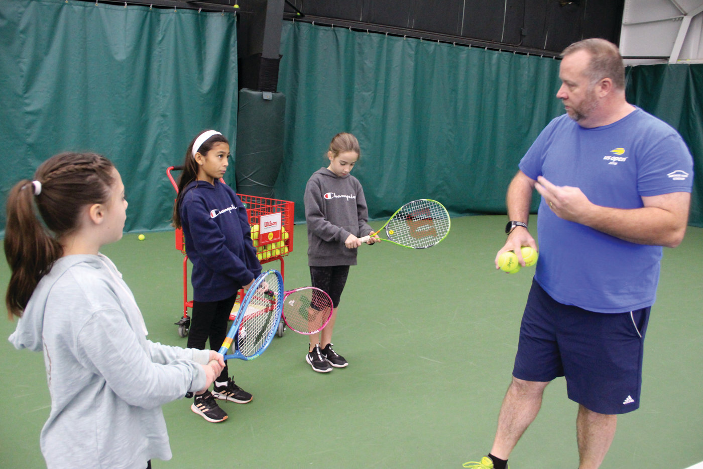 HOW IT'S DONE: Doug James has the girls practice a backhand swing before actually having them hit balls. Here he works with Autumn Koznar as Livia Xaykosy and Lexi Sky look on.