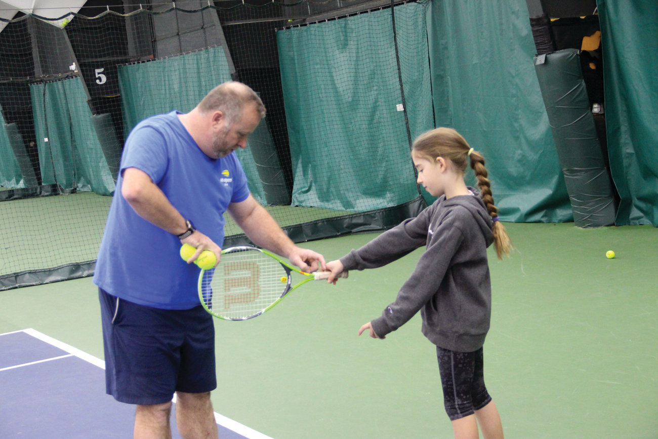 KEEPING A GRIP ON TENNIS: Doug James checks to see if Lexi Sky is holding her racket properly.