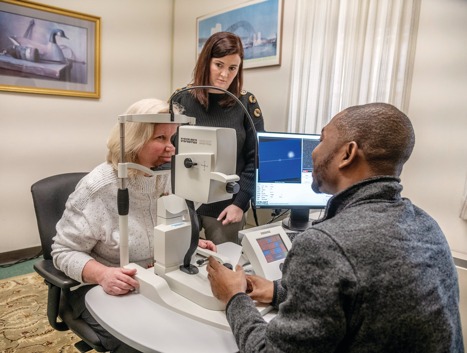 SETTING UP RETINAL SCANS: Team members of the Atlas of Retinal Imaging in Alzheimer's Study (ARIAS) Jessica Alber, Ph.D., Ryan research assistant professor of neuroscience at URI, standing, and Edmund Arthur, seated at right, doctor of optometry and Ph.D. and member of Alber's lab, work with Butler Hospital nurse (name) in preparation for a clinical trial using retinal scans to detect early signs of Alzheimer's disease.