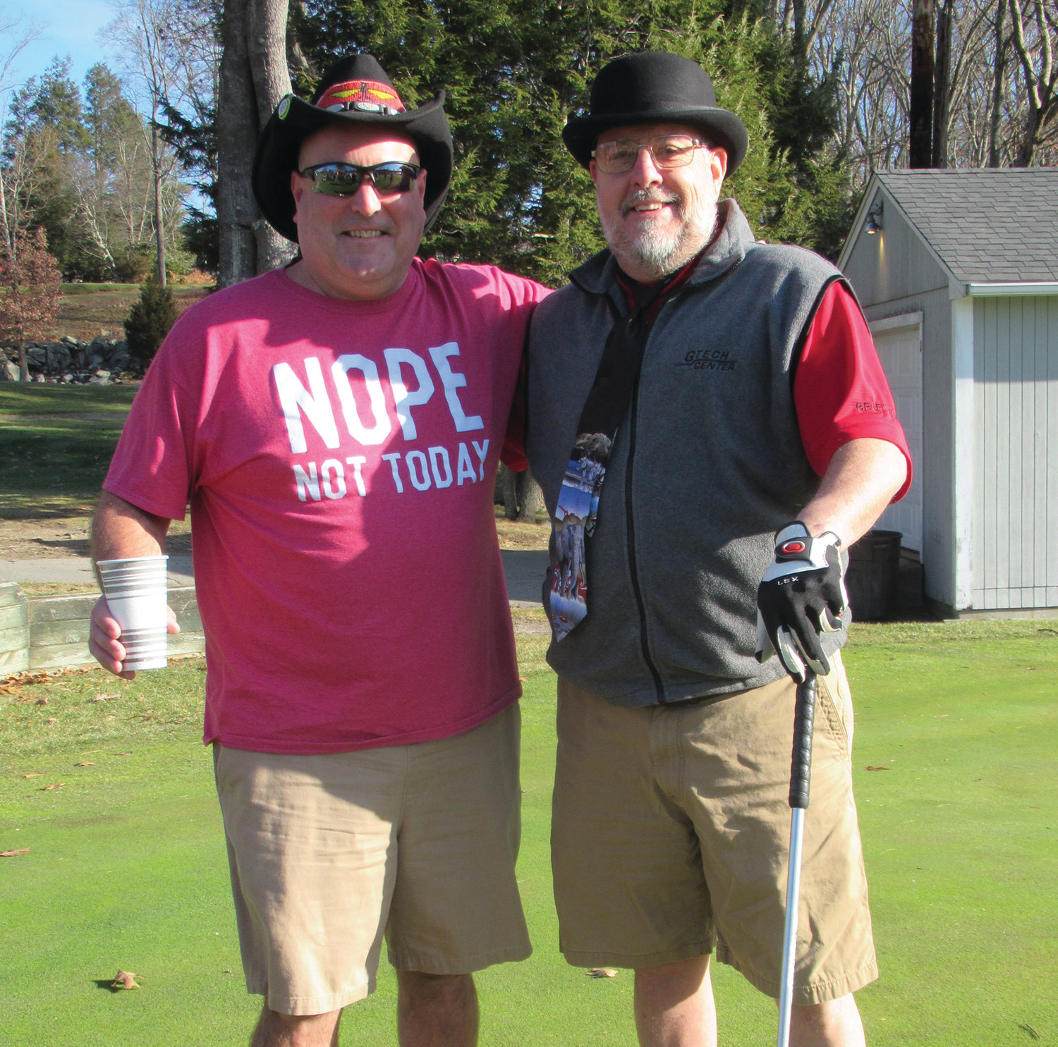 HAPPY HATS: John Martin (left) and David Graham enjoy a lighter moment modeling the respective hats they wore during the 6th annual Polar Golf Tourney.