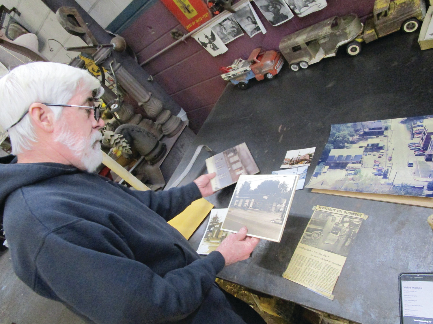 YEARS OF MEMORIES: Kevin McCrudden looks over images and newspaper clippings from the business's past during a Tuesday interview at his West Shore Road shop.
